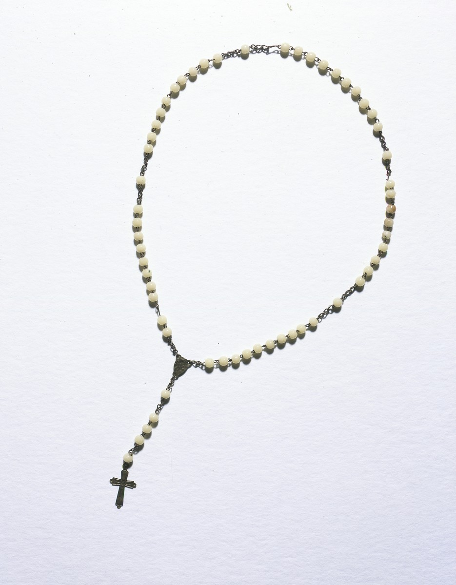 Rosary beads with a pendant crucifix given to the Jewish child, Lida Kleinman, while she was living in hiding in Poland during the German occupation.