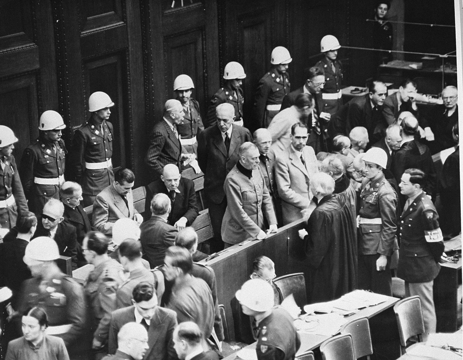 The defendants' dock during a recess at the International Military Tribunal trial of war criminals at Nuremberg.  Several of the defendants speak to their lawyers.