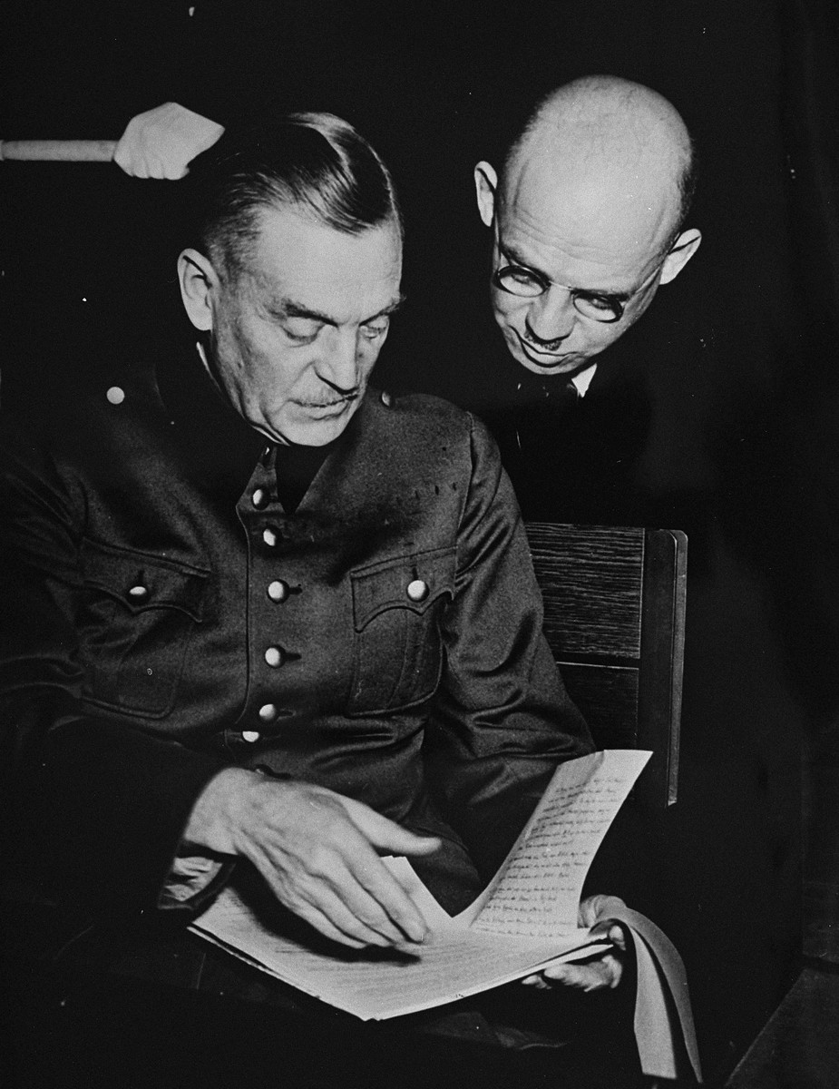 Defendants Wilhelm Keitel and Fritz Sauckel read over a document at the International Military Tribunal trial of war criminals at Nuremberg.