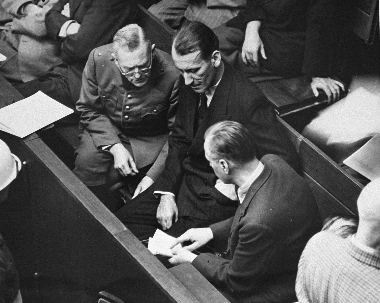 Defendants Wilhelm Keitel (left), Ernst Kaltenbrunner (middle), and Alfred Rosenberg (right), talk during a recess in the proceedings at the International Military Tribunal trial of war criminals at Nuremberg.
