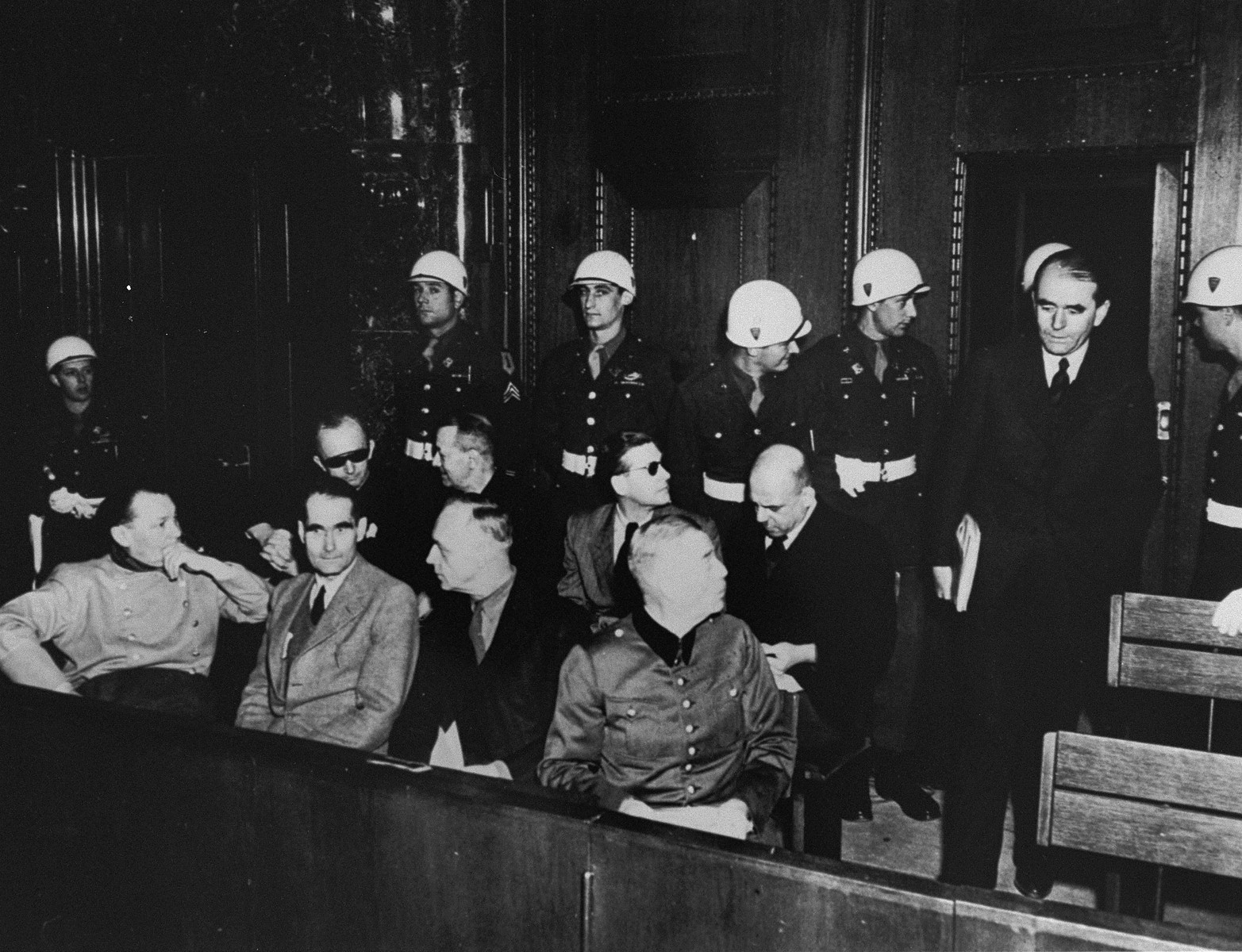 The defendants are led into the dock at the International Military Tribunal trial of war criminals at Nuremberg.  Pictured in the front row from left to right are: Hermann Goering, Rudolf Hess, Joachim von Ribbentrop and Wilhelm Keitel.  In the second row from left to right are: Karl Doenitz, Erich Raeder, Baldur von Schirach and Fritz Sauckel.