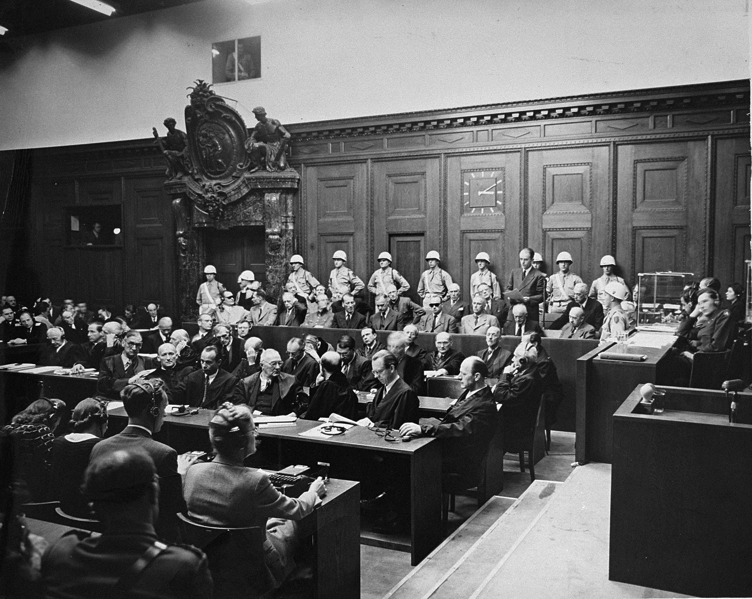 The defendants and their lawyers at the International Military Tribunal trial of war criminals at Nuremberg.  Defendant Albert Speer (standing at right) delivers a statement in the dock.