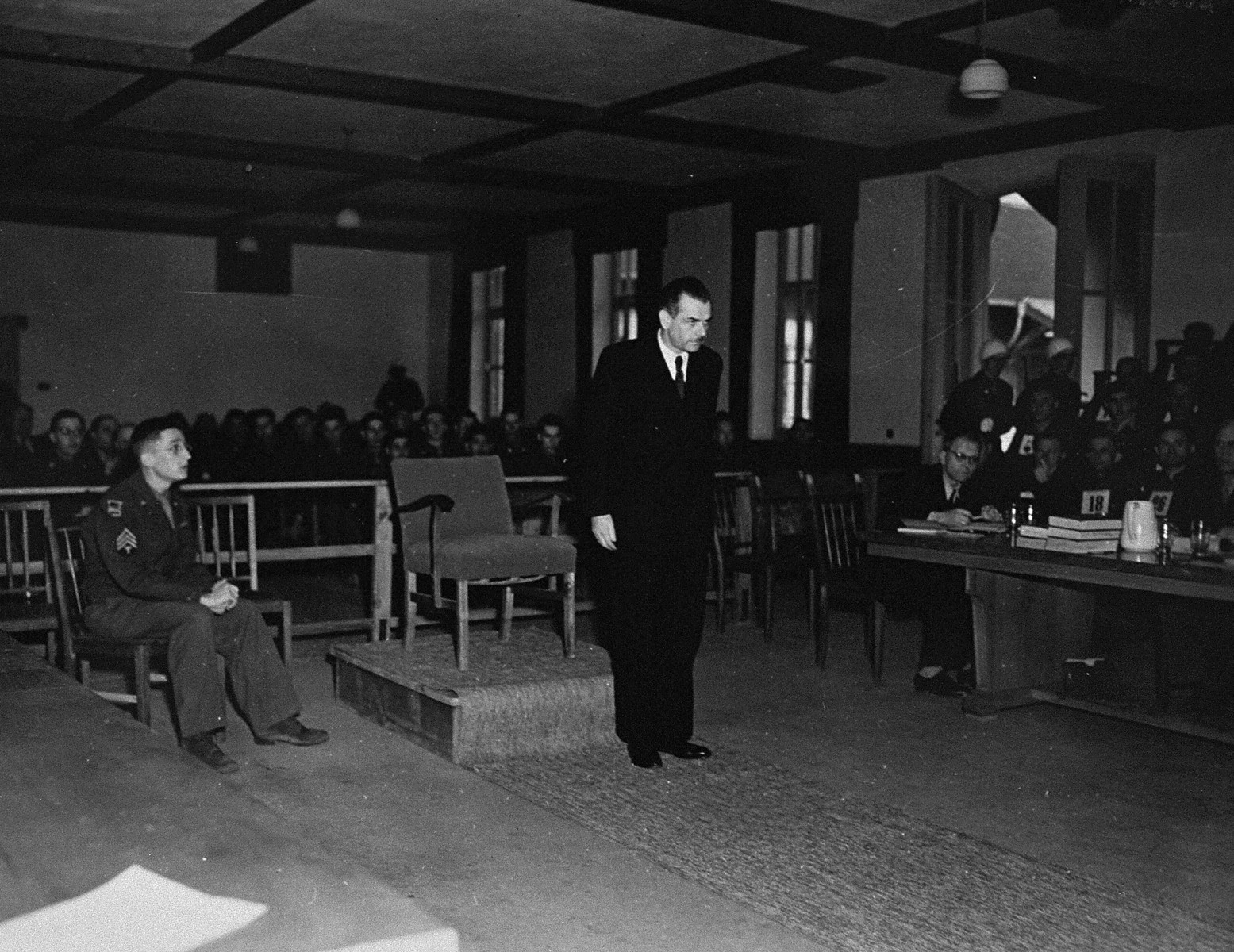 A witness at the trial of 61 former camp personnel and prisoners from Mauthausen.  On the left is Herbert Rosenstock, an interpreter.