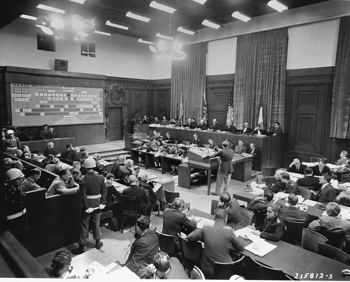 American Major Frank B. Wallis (standing), a member of the trial counsel and trial preparation legal staff, presents the prosecution's case to the International Military Tribunal at Nuremberg.    A chart (top left) shows where the defendants (bottom left) fit into the organizational scheme of the Nazi Party. At right are lawyers for the four prosecuting countries.