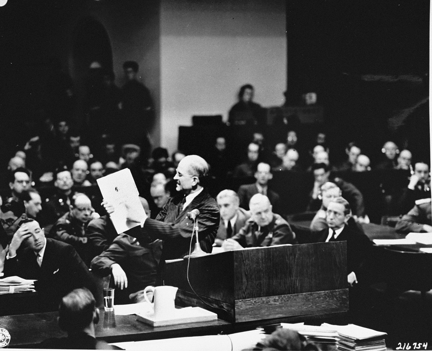 Executive trial counsel Colonel Robert G. Storey presents as evidence a document detailing Nazi intentions to launch an aggressive war, at the International Military Tribunal trial of war criminals at Nuremberg.