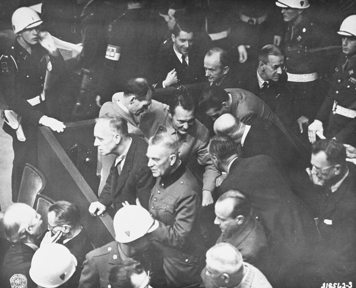 The defendants confer during a recess at the International Military Tribunal trial of war criminals at Nuremberg.  The guard in the upper right hand corner is possibly Albert P. Gobel.