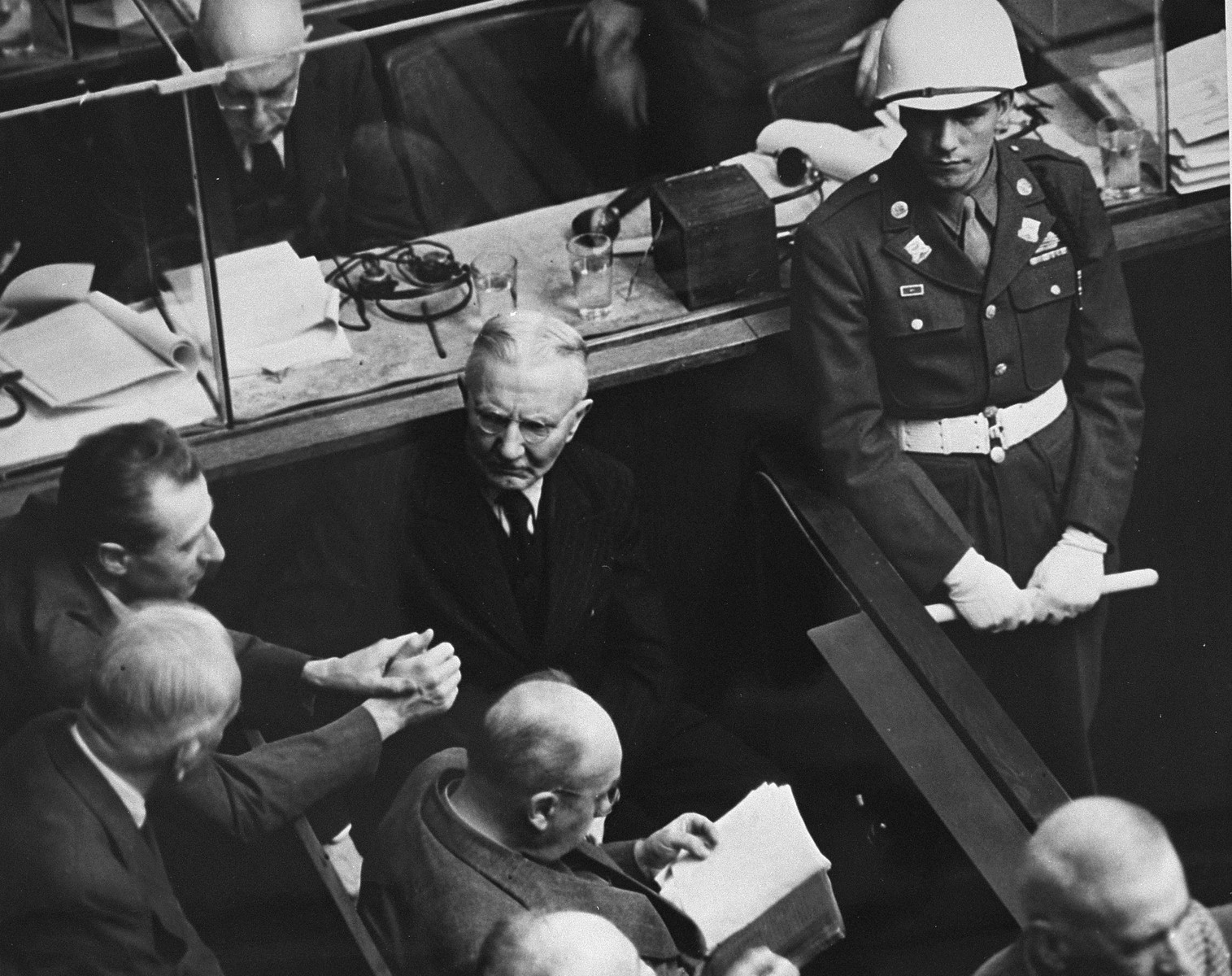 Defendant Hjalmar Schacht, former president of the Reichsbank, talks to his fellow defendants under the eye of an American military police officer at the International Military Tribunal trial of war criminals at Nuremberg.