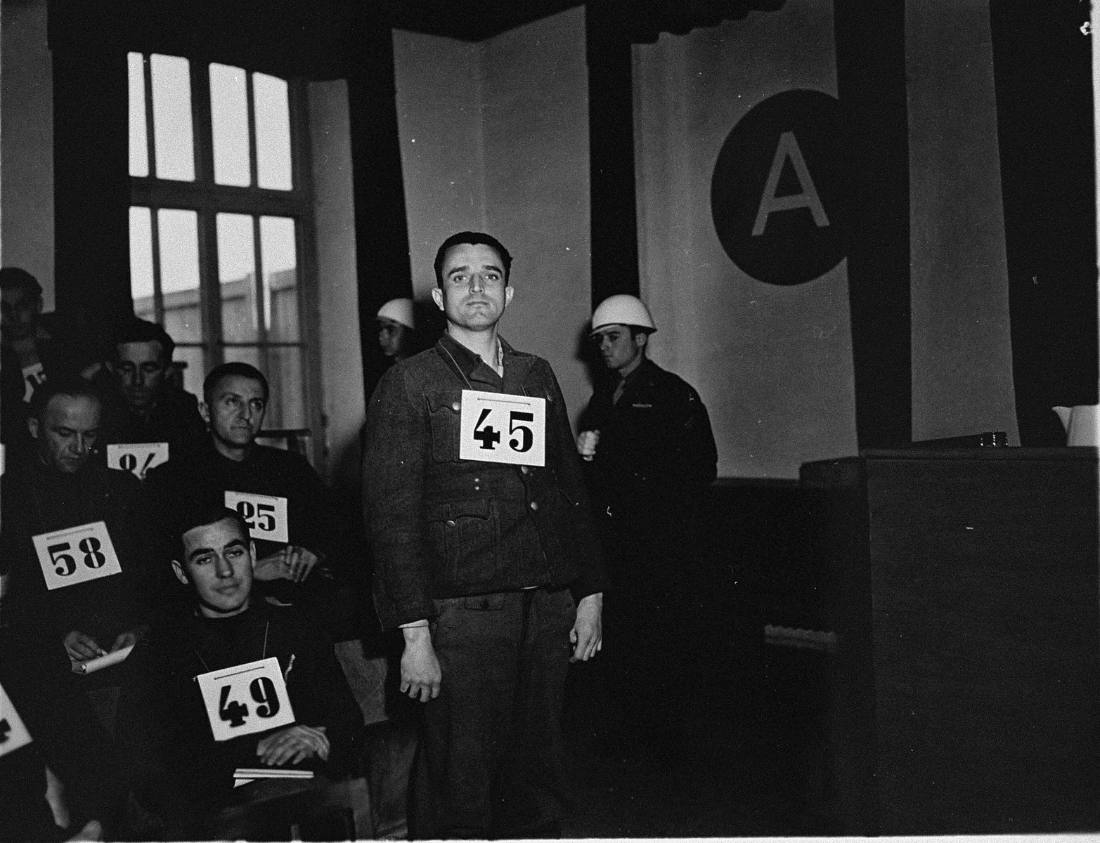 Former SS-Unterscharfuehrer Josef Niedermayer, a defendant at the trial of 61 former camp personnel and prisoners from Mauthausen, stands in his place in the defendants' dock.    Niedermayer was convicted and sentenced to death on May 13, 1946.