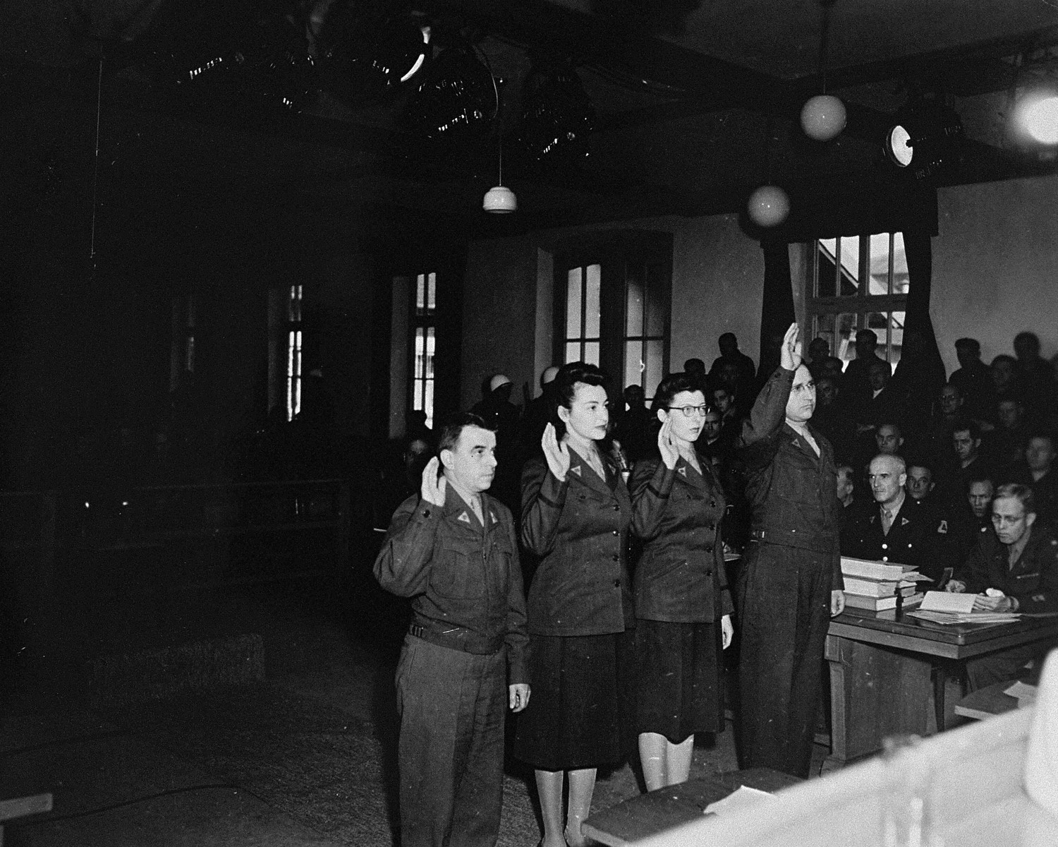 Four people (probably American court personnel) are sworn in at the trial of 61 former camp personnel and prisoners from Mauthausen.