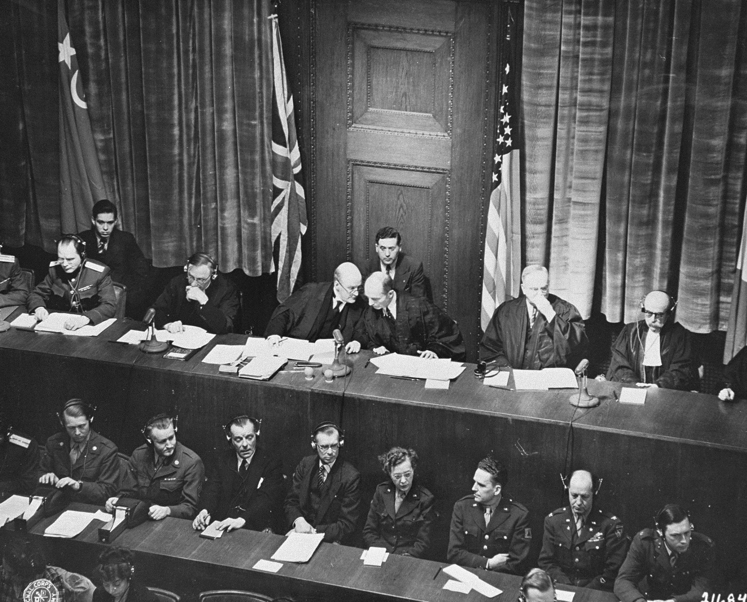 Tribunal members Lord Justice Geoffrey Lawrence (Britain, left) and Francis Biddle (U.S., right) confer at the opening session of the International Military Tribunal trial of war criminals at Nuremberg.