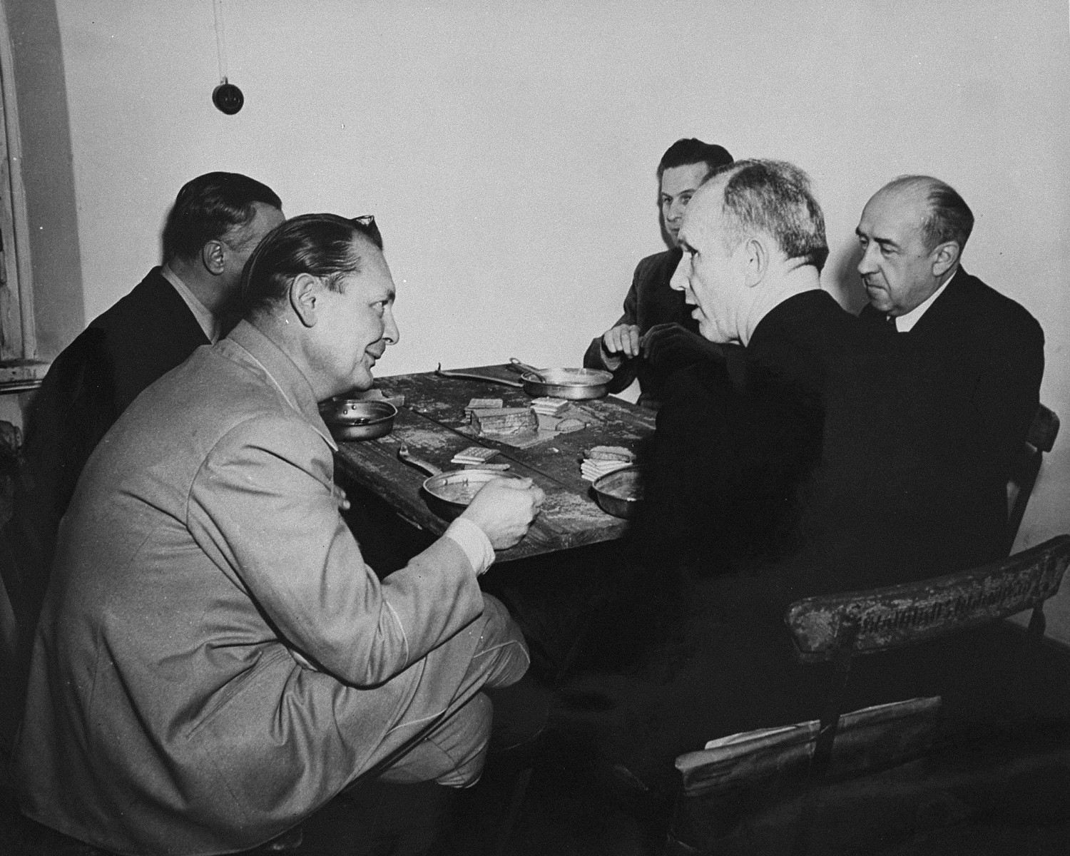 International Military Tribunal defendants eat lunch during a pause in the trial.  Pictured counterclockwise from the front left are: Hermann Goering, Karl Doenitz, Walther Funk, Baldur von Schirach, and Alfred Rosenberg.