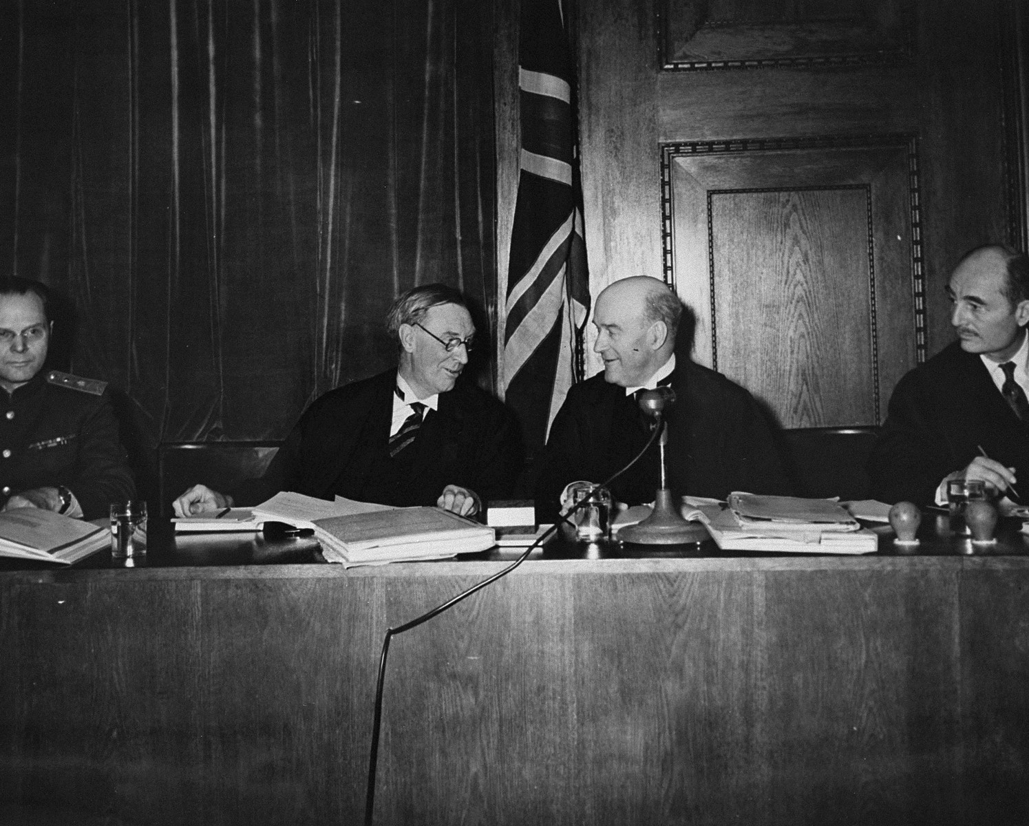 Four members of the International Military Tribunal sit on the bench in the courtroom in Nuremberg.  Pictured from left to right are: Major General I.T. Nikitchenko (Soviet), Justice Norman Birkett (British) Lord Justice Geoffrey Lawrence (British), and Francis Biddle (American).