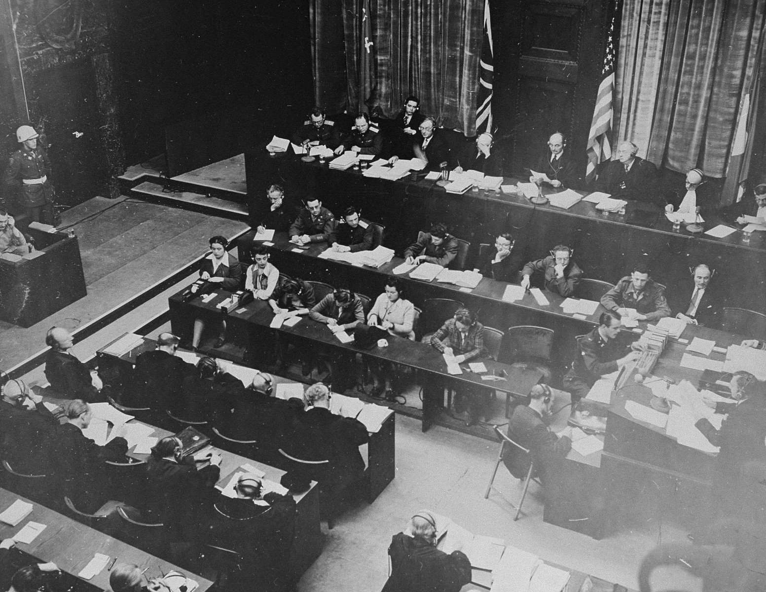 Chief U.S. prosecutor Justice Robert H. Jackson (bottom right) questions defendant Hermann Goering (seated left) during Goering's testimony before the International Military Tribunal (top) at the trial of war criminals at Nuremberg.