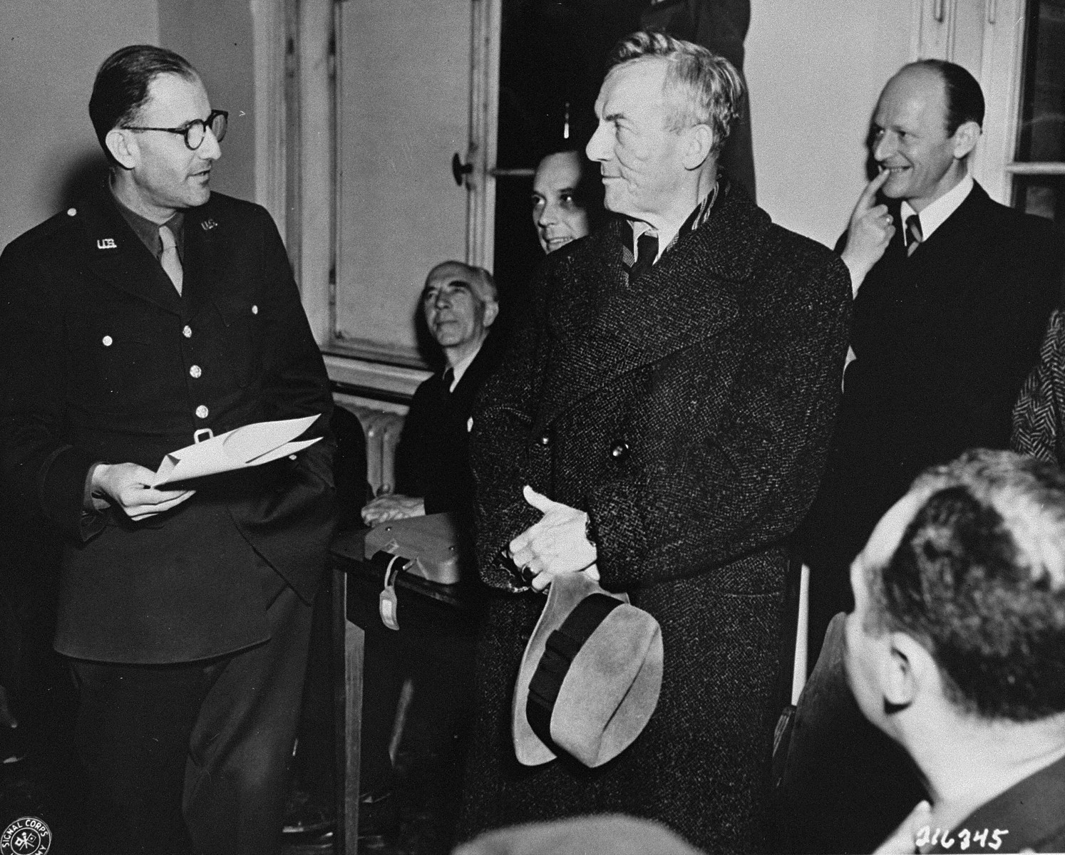 Dr. Hans Marx, the lawyer representing Julius Streicher, is introduced to a roomful of news correspondents before the beginning of the International Military Tribunal trial of war criminals at Nuremberg.