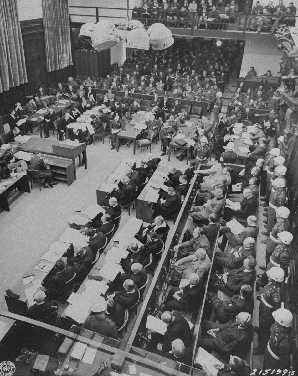 The opening of the proceedings at the International Military Tribunal of war criminals at Nuremberg.  In view are the defendants (bottom right), their lawyers (bottom middle), the prosecution tables (left to right in the middle), and spectators (top).  Standing at left, a prosecution lawyer reads an indictment.