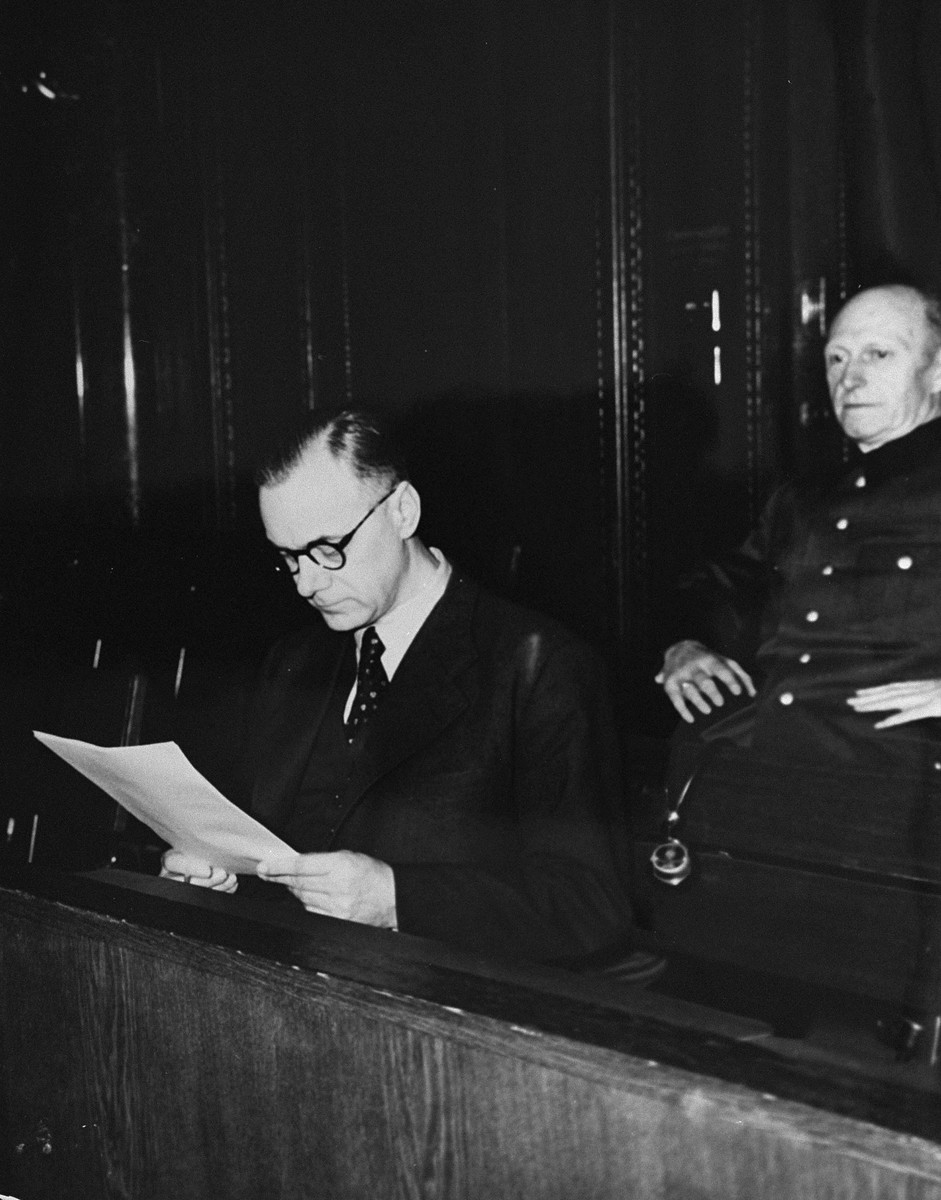 Defendant Alfred Rosenberg, the former Chief Nazi Party ideologist, reads a document during the International Military Tribunal trial of war criminals at Nuremberg.  Behind him is his co-defendant General Alfred Jodl, formerly the Chief of Staff for the Army.