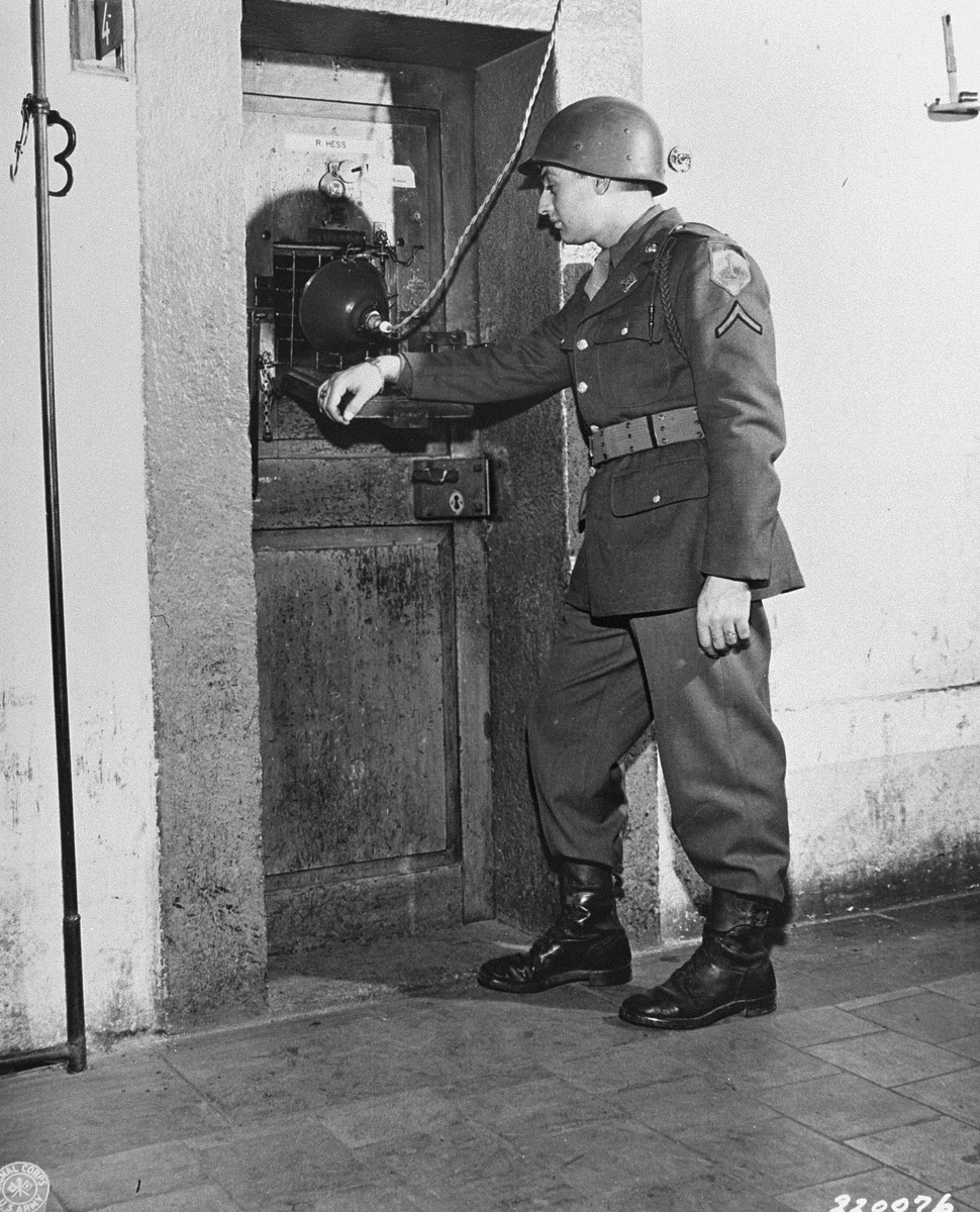 At the prison in Nuremberg, Pfc. Joseph L. Pichierre guards the door to the cell of Rudolf Hess, a defendant at the International Military Tribunal trial of war criminals.