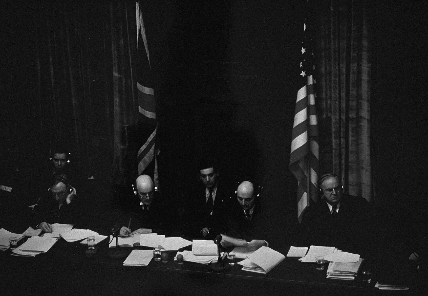 The British and American judges on the International Military Tribunal listen to testimony through their headphones at the trial of war criminals at Nuremberg.    Pictured from left to right are: Justice Norman Birkett, Lord Justice Geoffrey Lawrence, Francis Biddle, and John J. Parker.