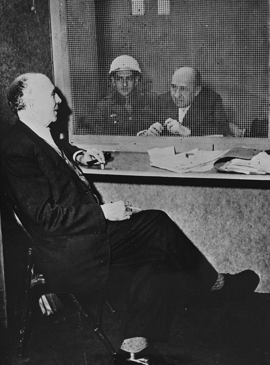 Defendant Walther Funk, former Reichsminister of Economics, speaks with his defense attorney, Dr. Fritz Sauter, in a visitation room at the International Military Tribunal trial of war criminals at Nuremberg.