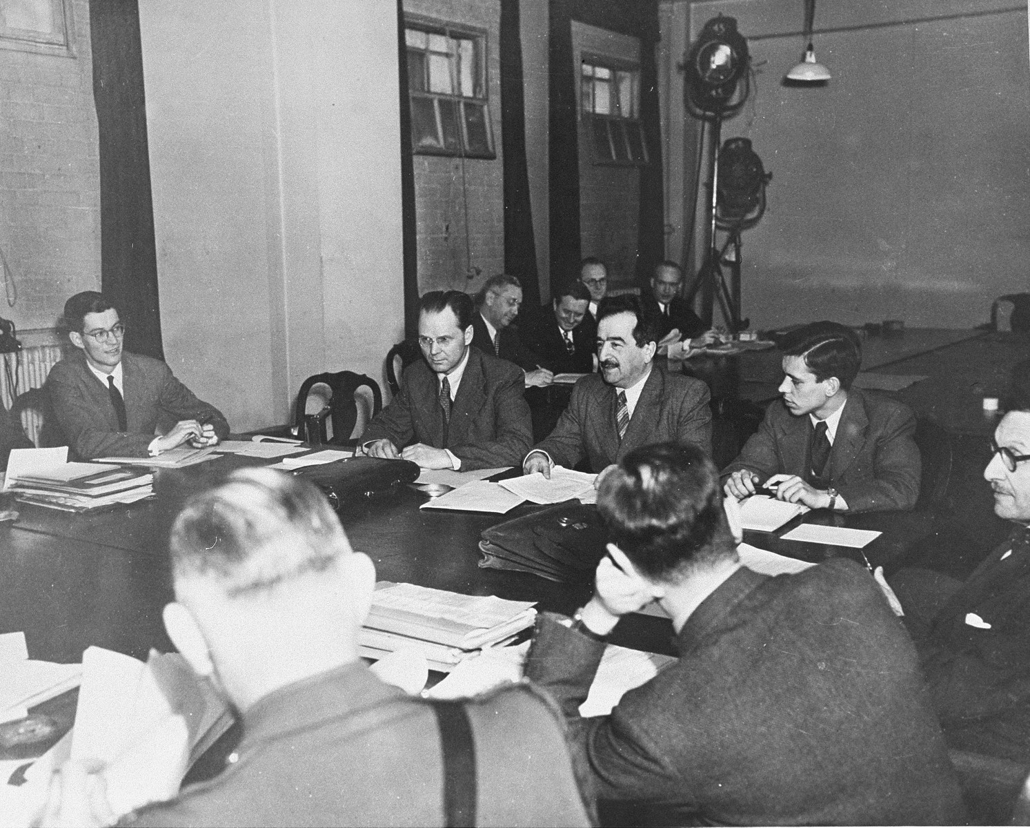 A.N. Trainin (center with mustache), head of the Soviet delegation to the War Crimes Executive Committee, speaks to his colleagues.    To his right sits I.T. Nikitchenko, who later represented the U.S.S.R. on the International Military Tribunal.  This body worked out the Allied agreement to create the International Military Tribunal to prosecute German war criminals at Nuremberg.