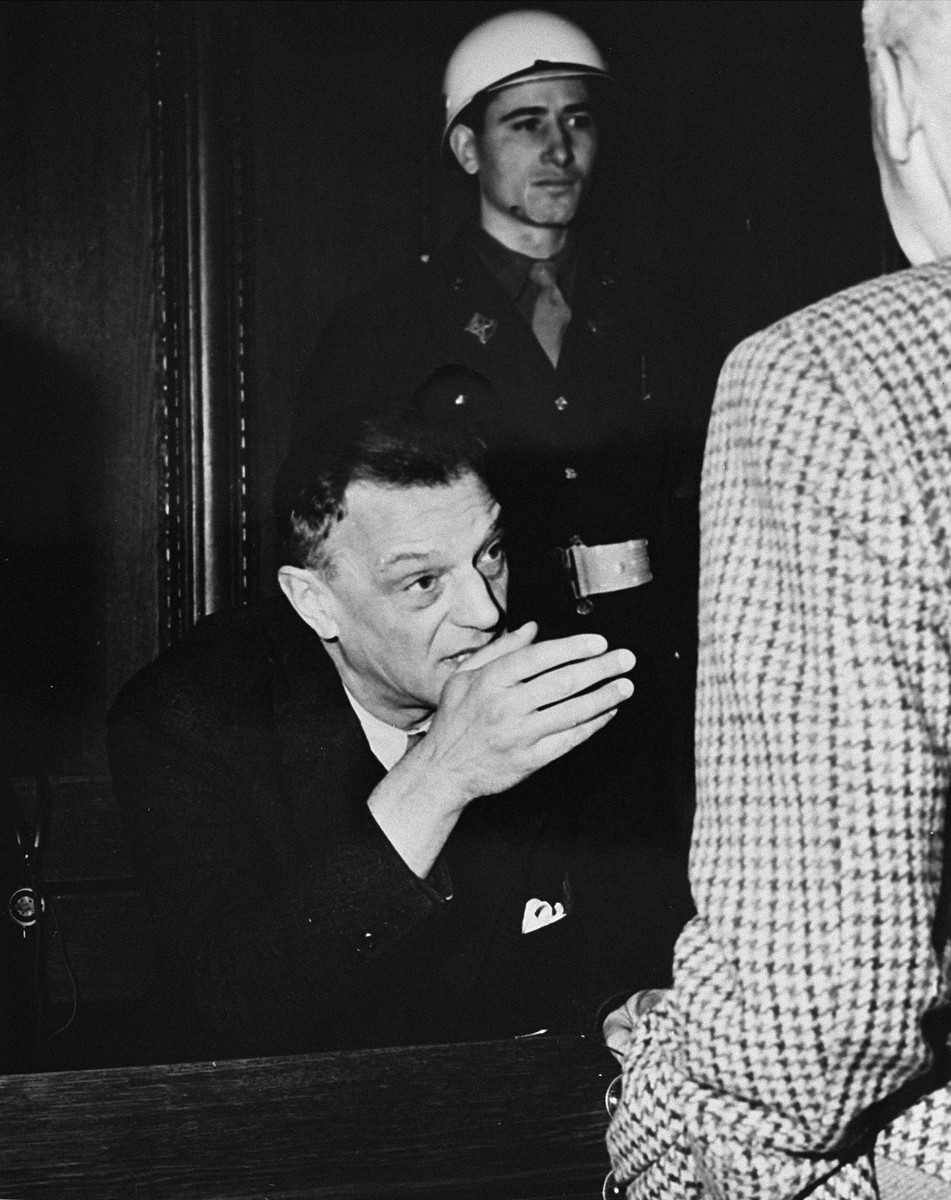 Defendant Arthur Seyss-Inquart talks to fellow defendant Wilhelm Frick during a court recess at the International Military Tribunal trial of war criminals at Nuremberg.