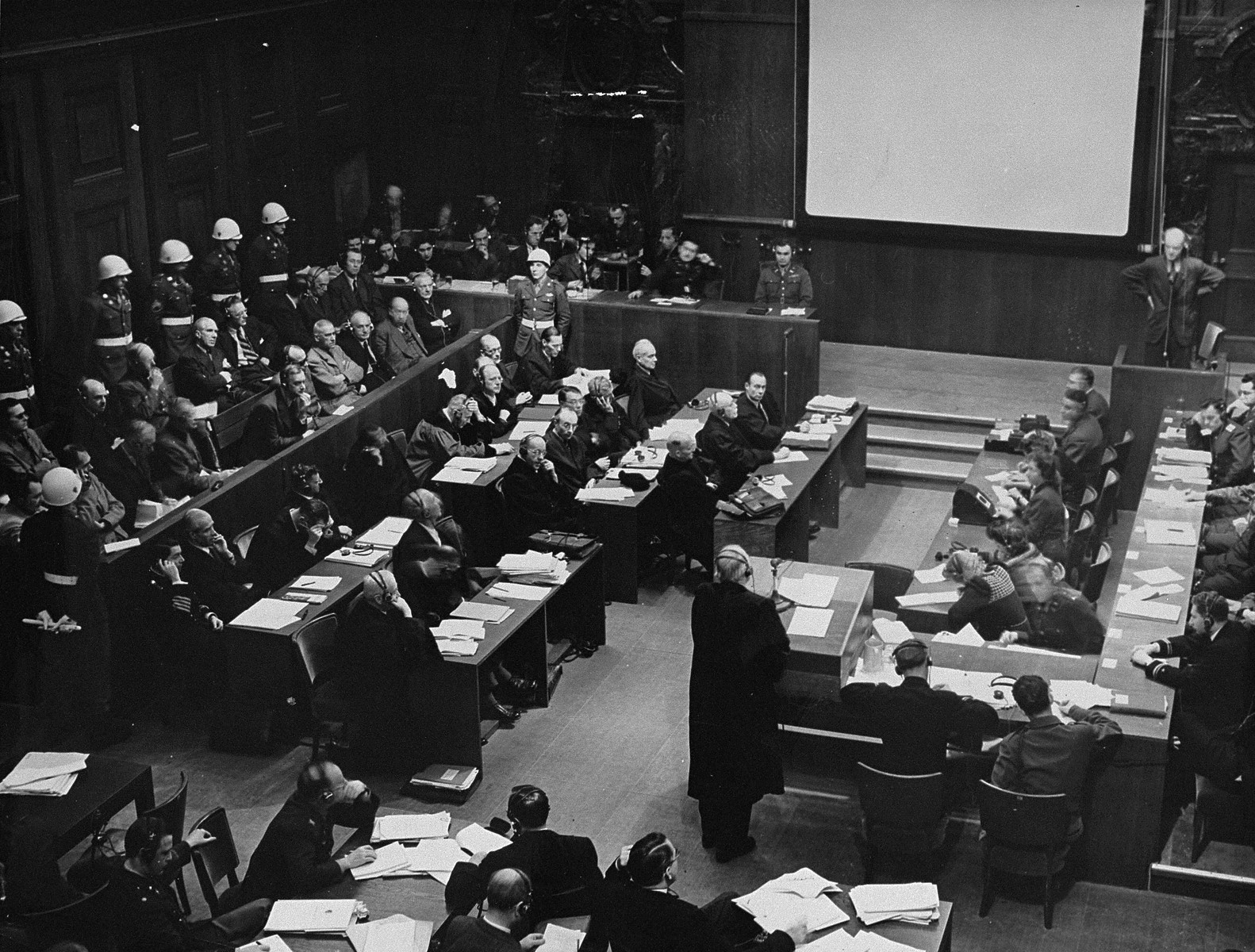 """Dr. Nelte, defense attorney for Wilhelm Keitel, questions a witness at the International Military Tribunal trial of war criminals at Nuremberg.  Pictured at the upper left is the interpreters box.  To the right of the box is the coordinating monitor who regulates the speed of the speakers voice by flashing either a red light meaning """"stop"""" or a yellow one, meaning """"slow down.""""  Sitting beside him (below the screen) is Col. Mays, the marshall of the court who is responsible for order in the courtroom while the tribunal is in session.  The defendants dock is pictured at the left.  In front of them are the defense counsel sitting at five tables.  Facing them on the right are the court reporters."""