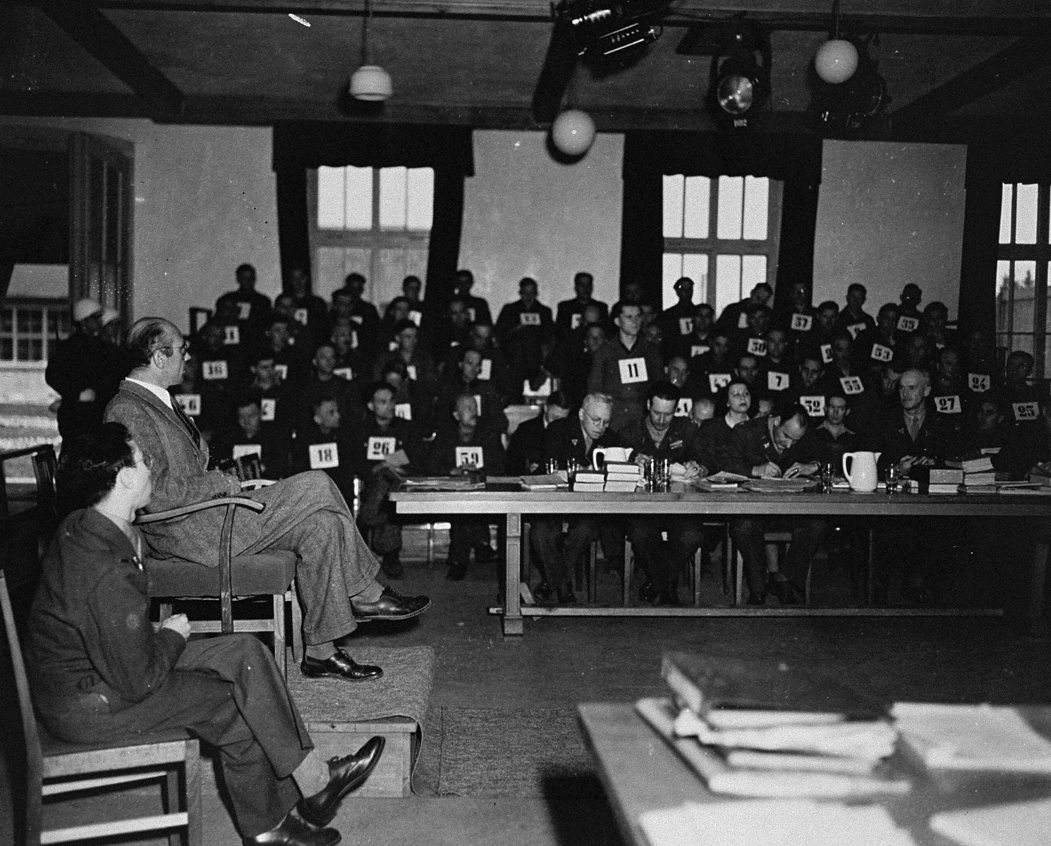 A witness testifies at the trial of 61 former camp personnel and prisoners from Mauthausen.  The man standing in the background is defendant Willy Eckert, a member of the SS.