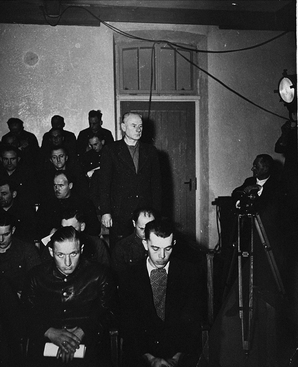 Dr. Eduard Krebsbach, a defendant at the trial of 61 former camp personnel and prisoners from Mauthausen, stands in his place in the defendants' dock.
