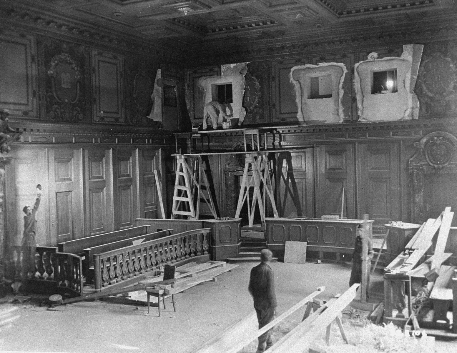 Repairs and improvements are made to the courtroom where the International Military Tribunal trial of war criminals will be held.  The holes in the walls at the top will house radio commentators and public address operators.