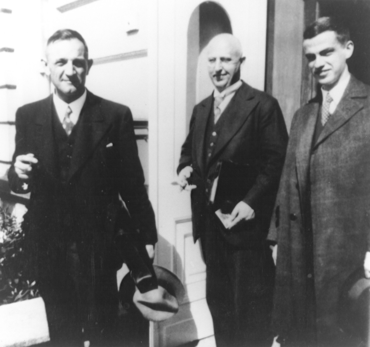 Pastor Martin Niemoeller poses in a doorway with two other clergymen from the German Confessing Church in Berlin during the Third Reich.   On the right is the vicar Franz Hildebrandt.  Ina the middle is Fritz Mueller.