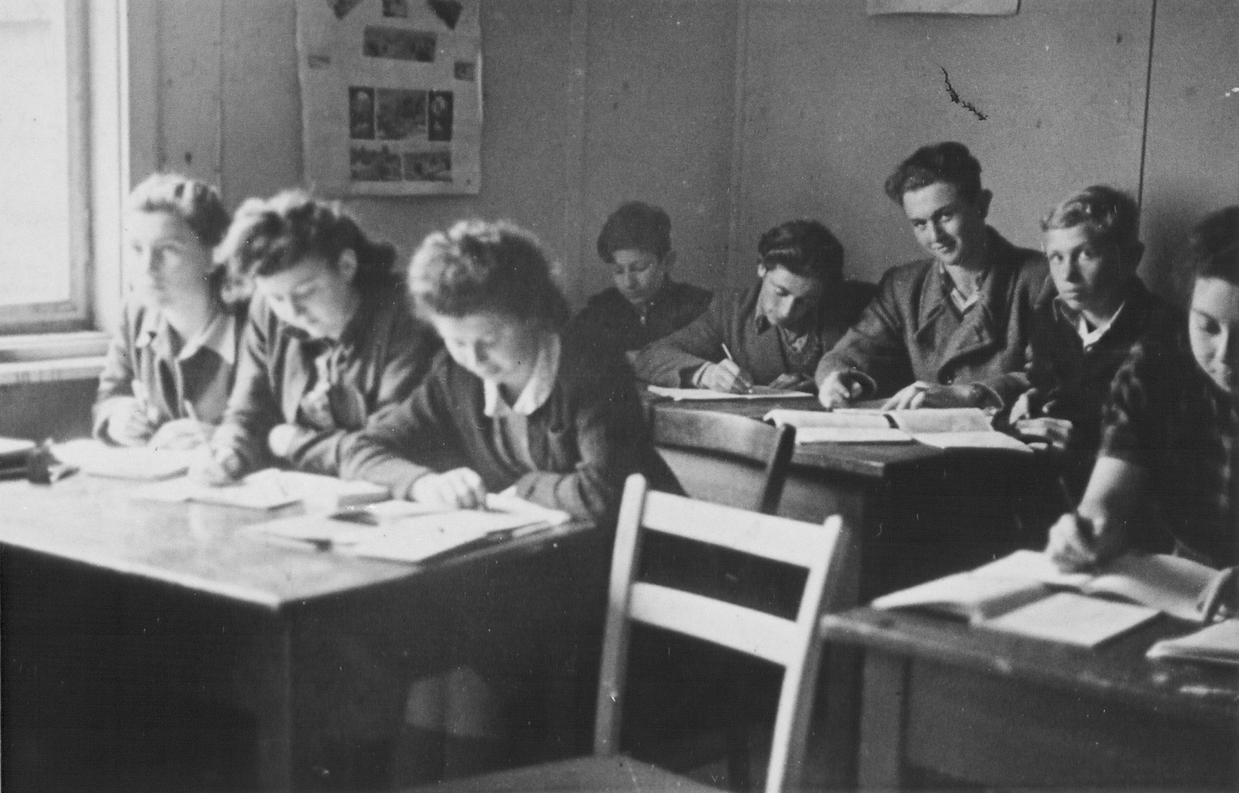 Jewish DP youth study in a high school classroom at the Schlachtensee displaced persons camp.    Among those pictured is Regina Laks (front row, right).