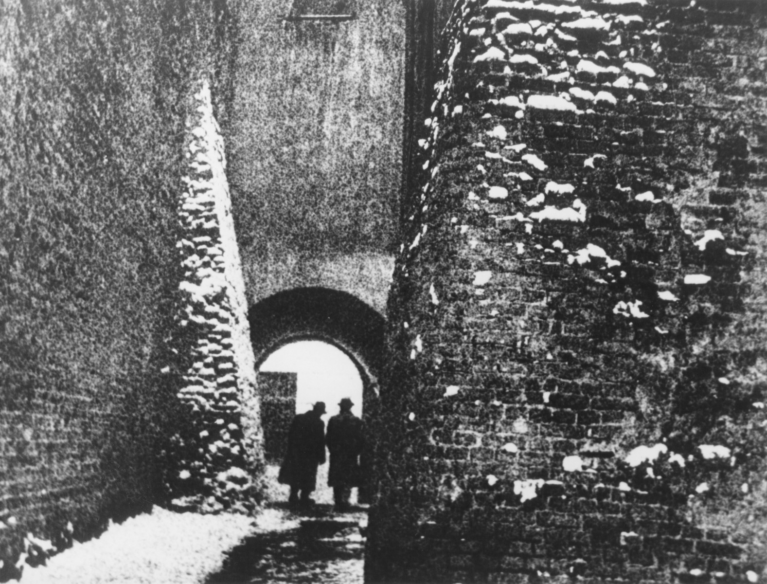 Two men walk through the archway on the Ku Farze alley in Lublin.