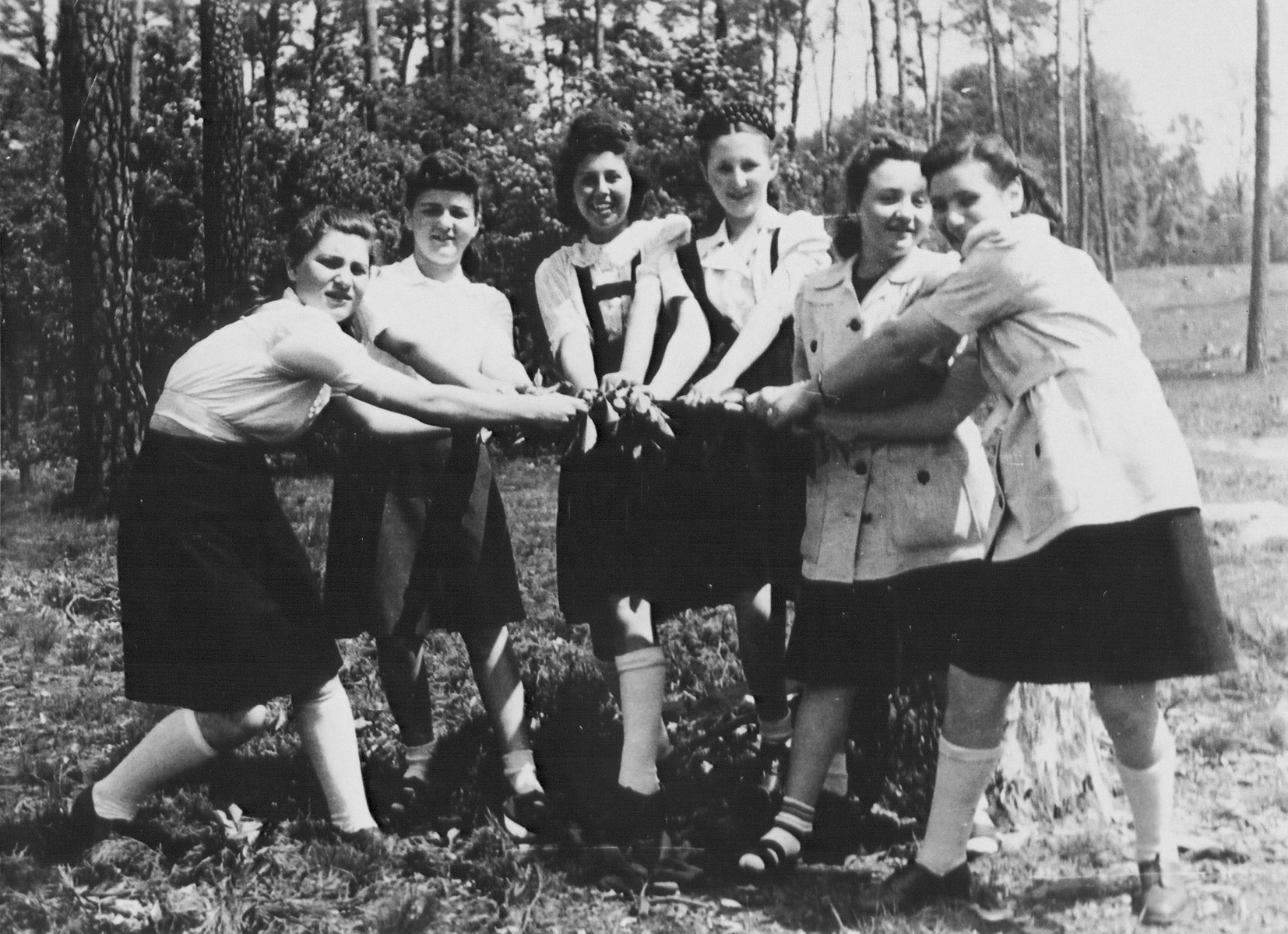 A group of Jewish DP girls from the Schlachtensee displaced persons camp pose outside with their hands joined during a Shavuot holiday outing.    Among those pictured is Regina Laks (third from the left).