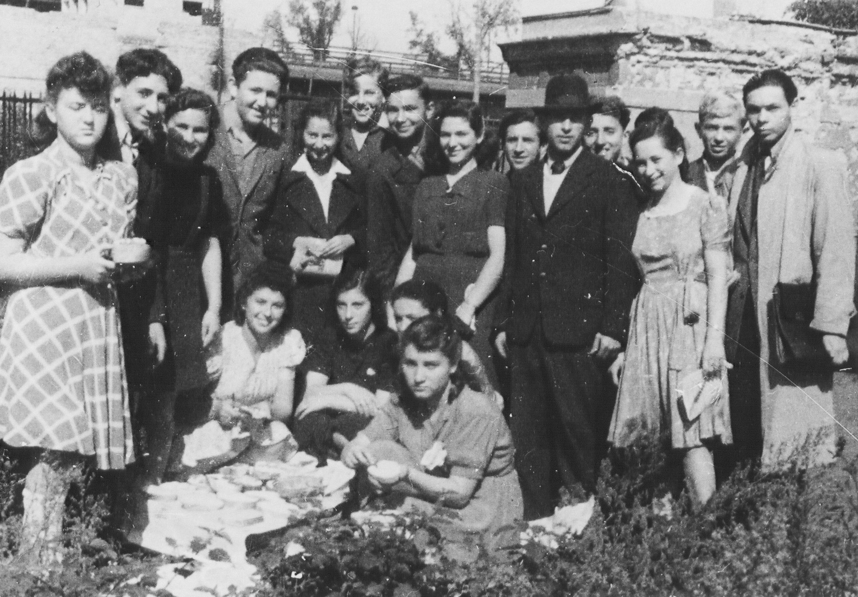Group portrait of Jewish DP youth at a picnic in the Schlachtensee displaced persons camp.    Among those pictured is Regina Laks (squatting on the left) and the English teacher (far right).