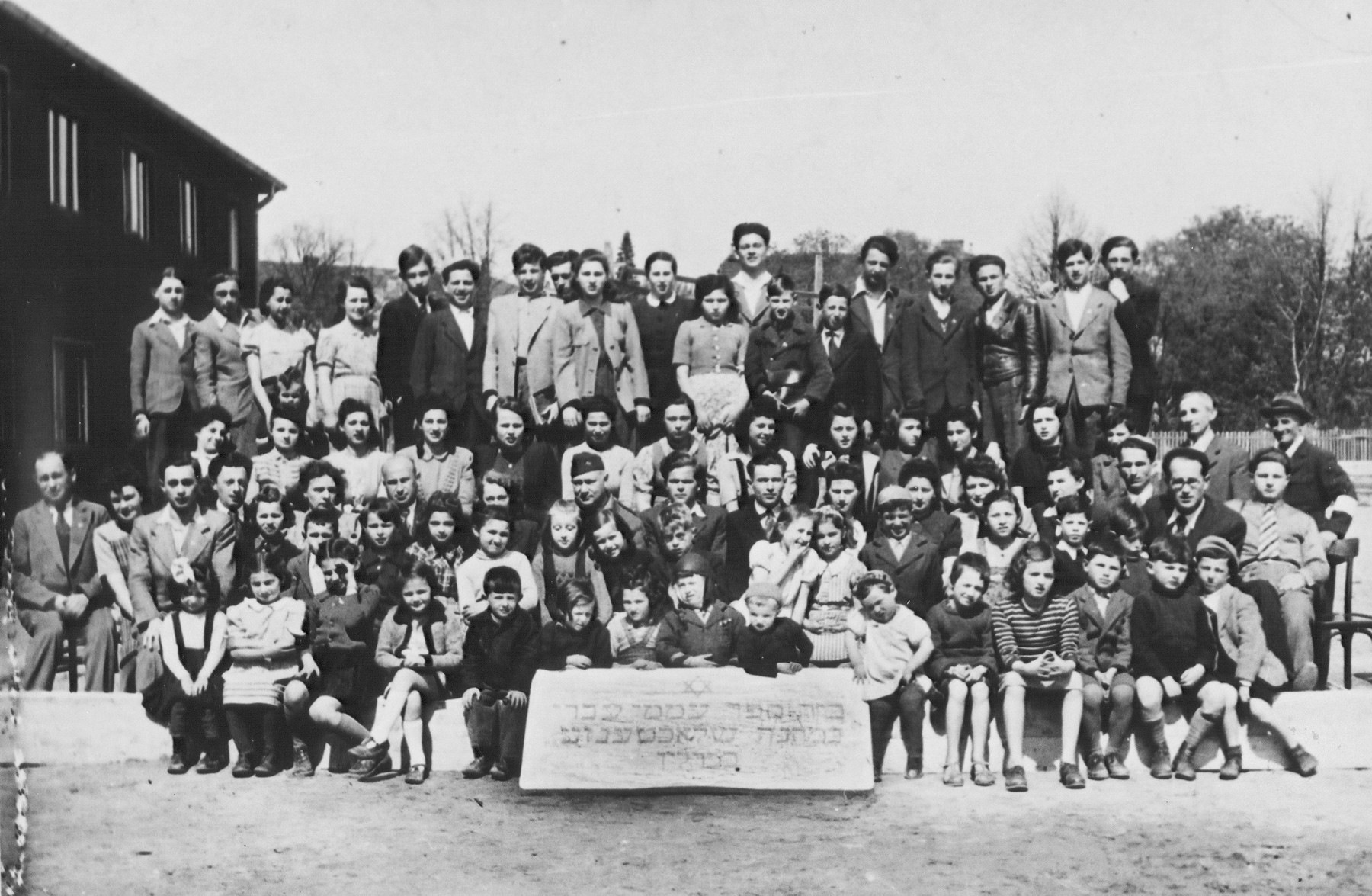 Group portrait of the students and teachers of the Hebrew primary school in the Schlachtensee displaced persons camp.    Among those pictured is Harold Fishbein (third row from the front, center wearing the soft military cap) and Regina Laks (fourth row center).