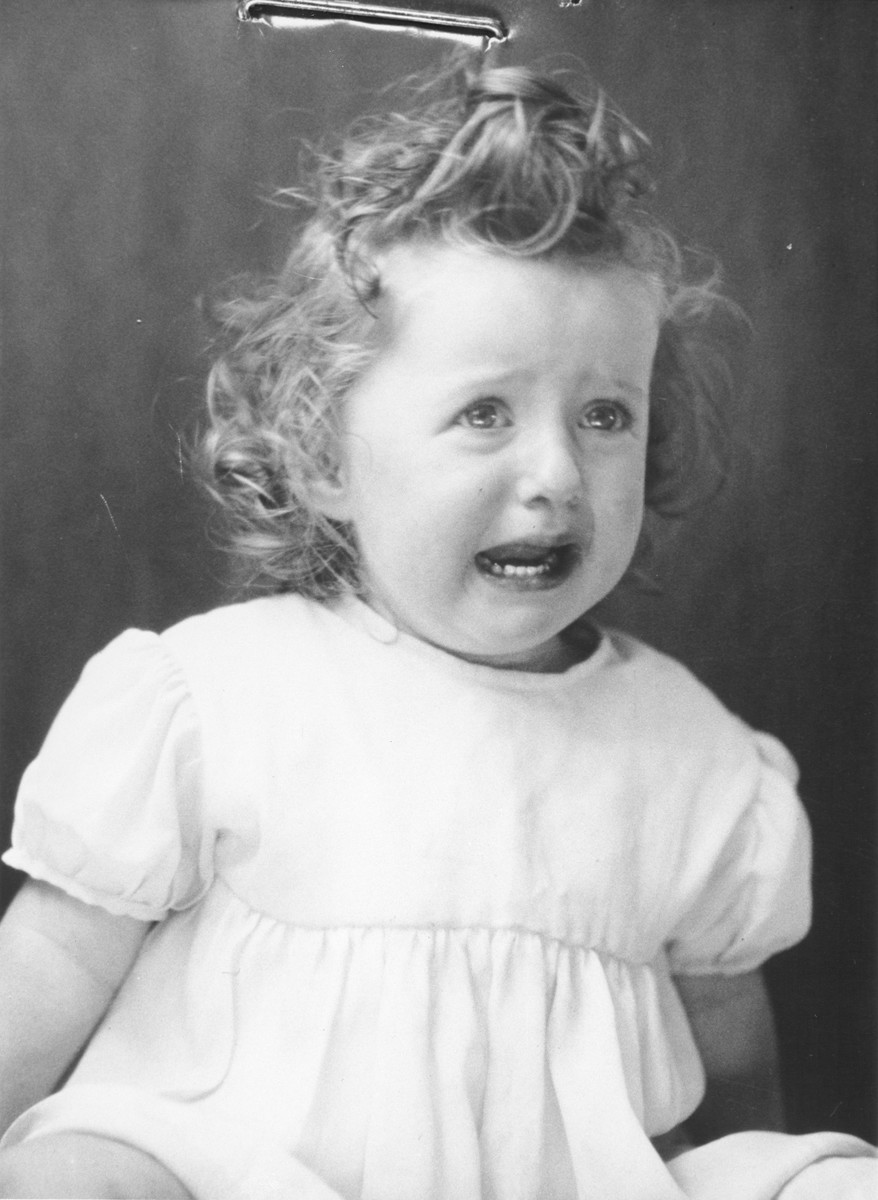 Portrait of a Jewish refugee child from Belgium taken by the Swiss police after she escaped with her family from occupied France into Switzerland in the fall of 1943.  Pictured is Mania Wajsfeld.
