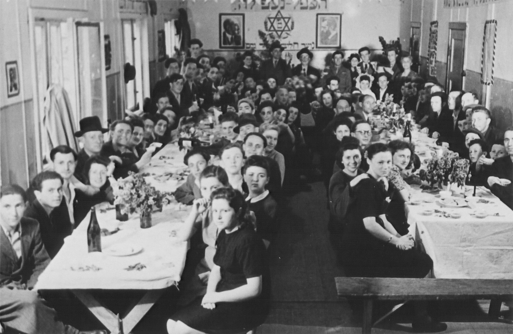 Jewish DPs are gathered around long tables at a [wedding] celebration in the Schlachtensee displaced persons camp.