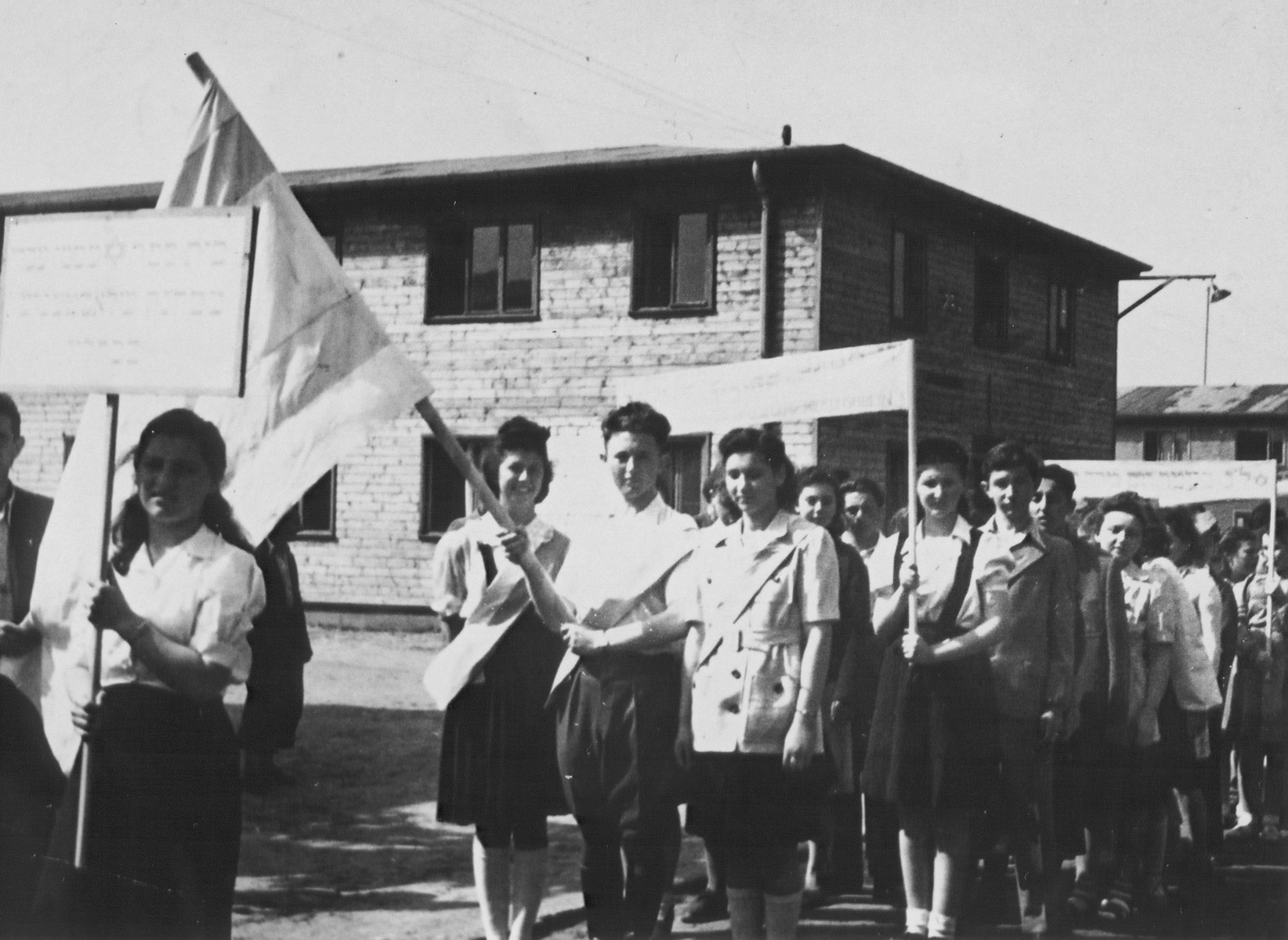 Jewish DP youth march with flags and banners in a Zionist demonstration at the Schlachtensee displaced persons camp.    Among those pictured is Regina Laks (on the left next to the flag).  Also pictured are Hanka Drescher (holding sign?), Salek Schulman, Lucia Weidberg, Tunka (last name unknown), Reyna (last name unknown), and Helen Friedman.