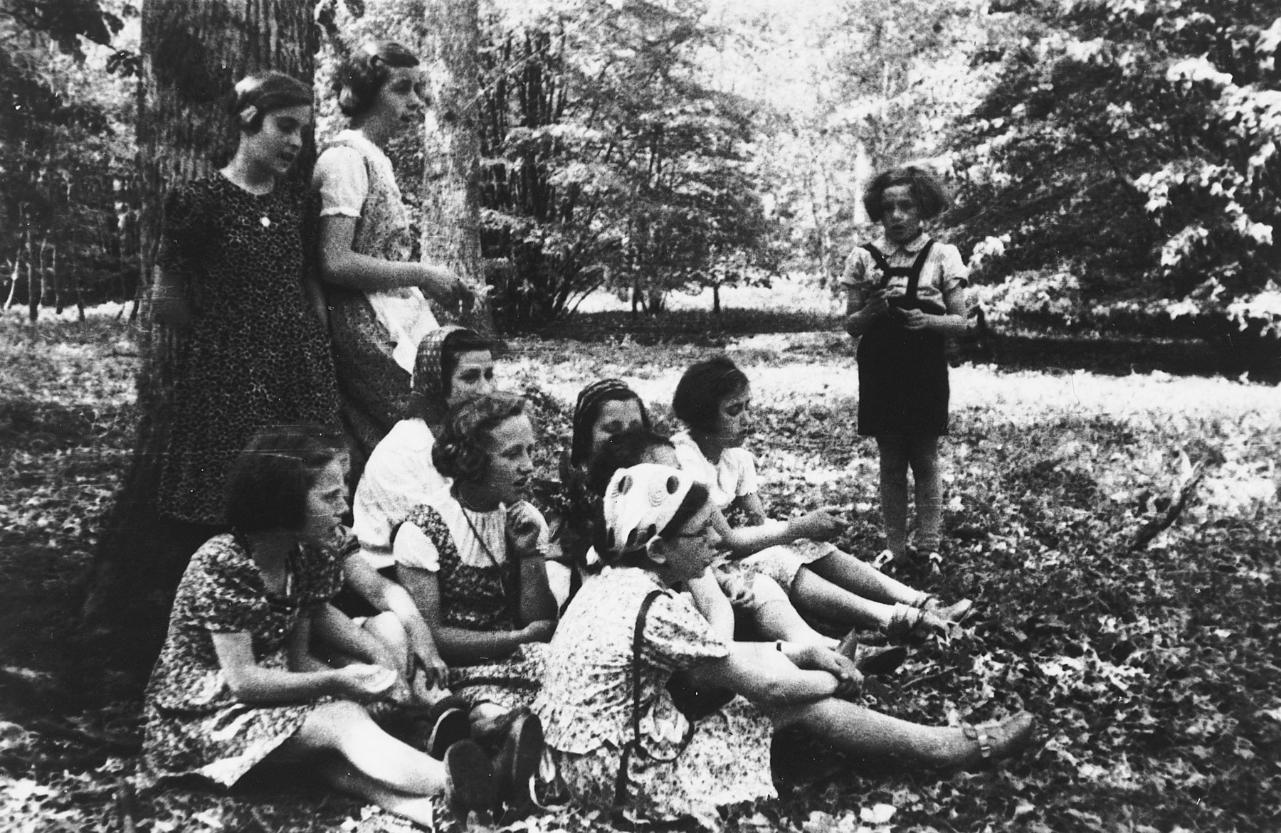 Young Jewish girls from Germany and Austria relax on the grounds of La Guette children's home the summer before the start of World War II.  Among those pictured are Ruth Strauss and Daisy Herman leaning against the tree, and Alice Menkes facing the other girls.  The young girl sitting on the ground at the far left is Hilde Mann (later Hilde Michele Simenauer).
