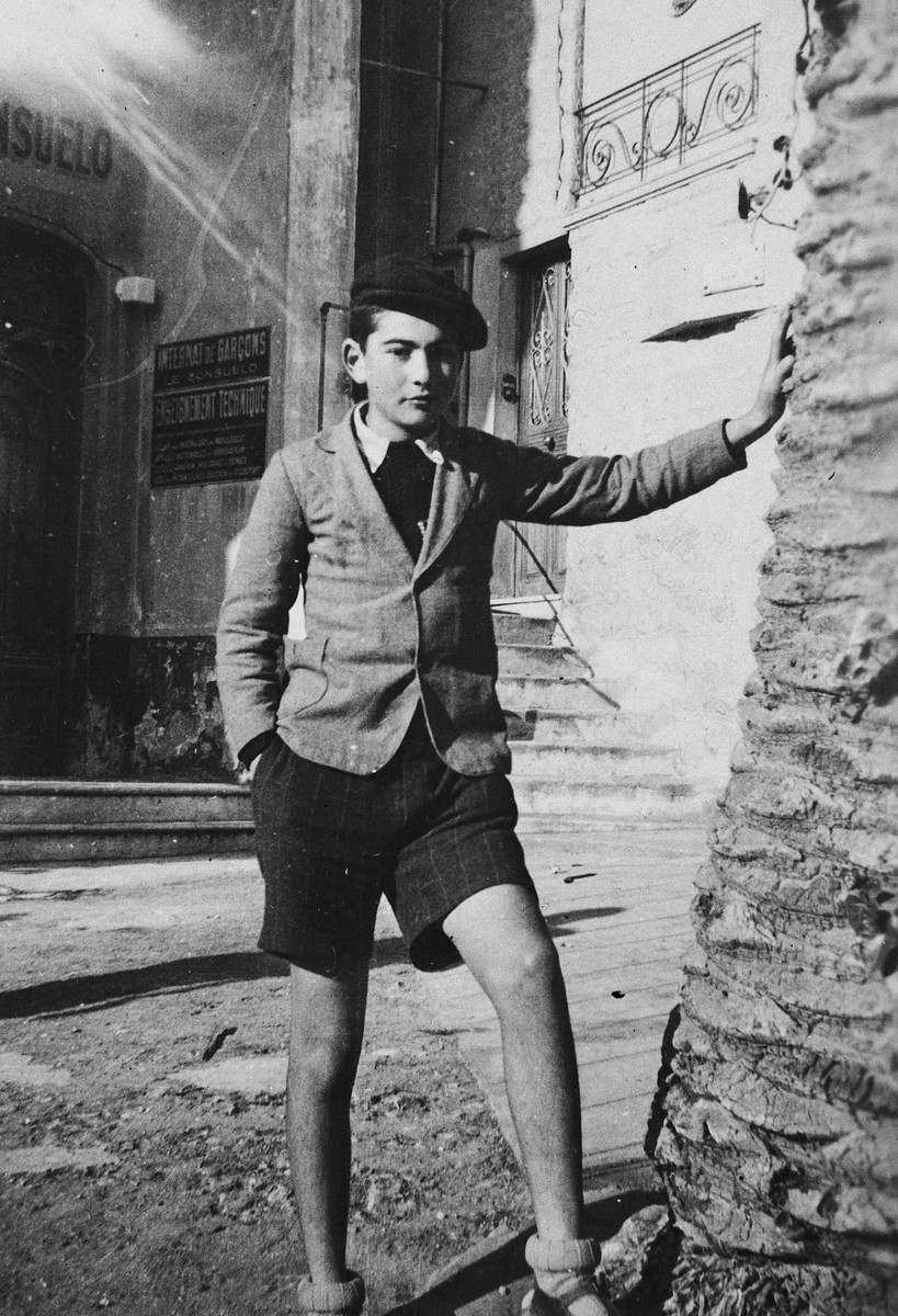 Paul Peter Porges, leans against  a palm tree on a street in Nice.