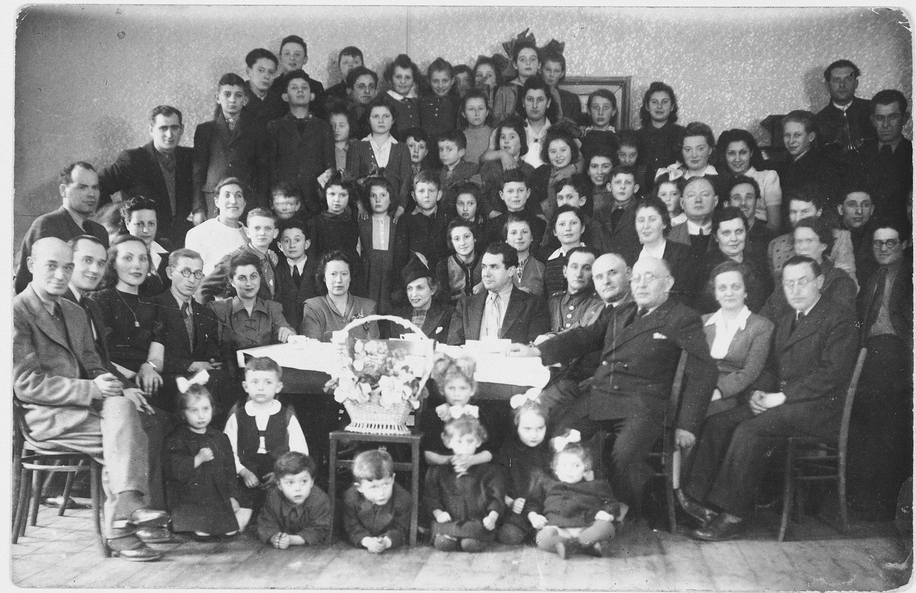 Yiddish actress Ida Kaminska visits the children and staff of a children's home in Chorzow, Poland.