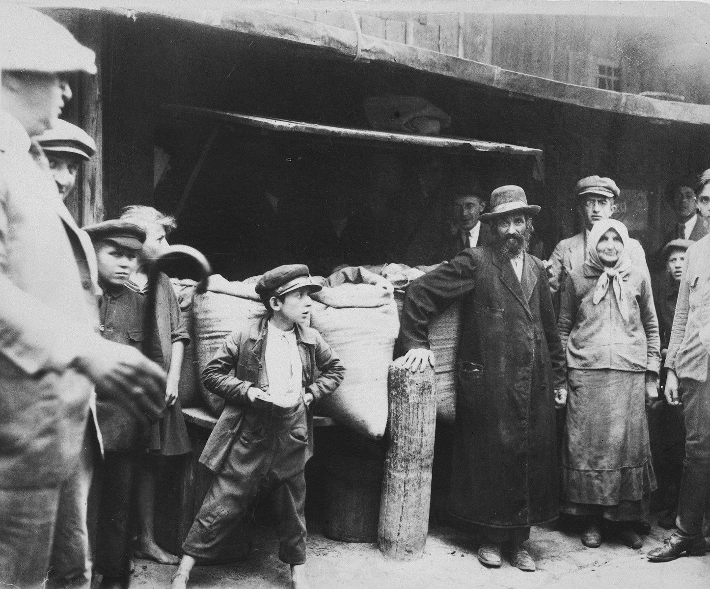 A Jewish family poses in front of their grains stall in the Drohobycz marketplace.  On the far left is Harry Handel, a relative from America.  On the right is the grandmother of the donor.