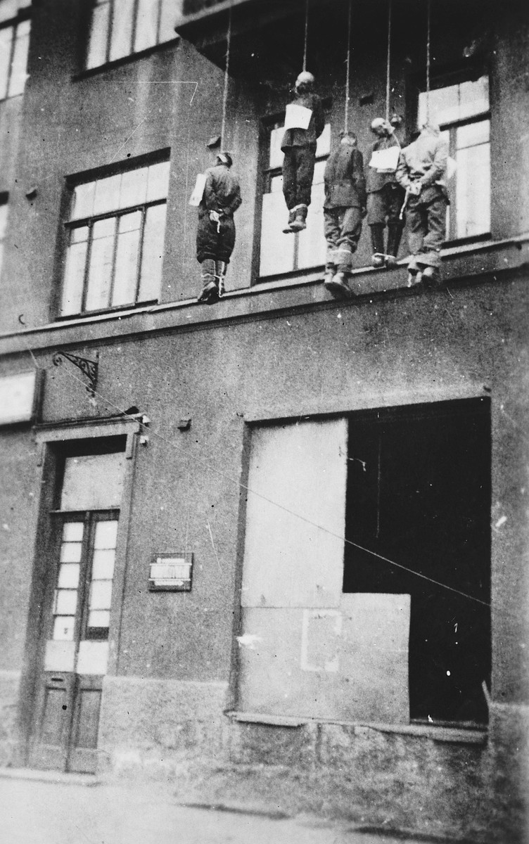 The bodies of five civilians executed by German forces hang from the balcony of a building in an unidentified city.  Each of the victims wears a sign around his neck.