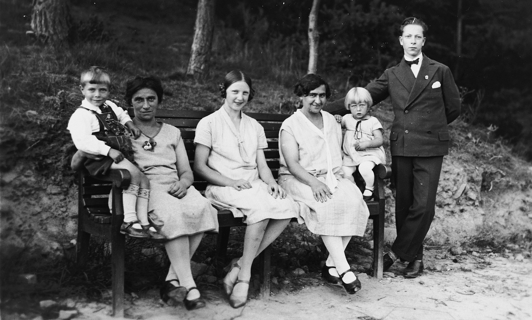 A German-Jewish family poses on a park bench.  Johanna Leopold Kuemmel is on the far left with her son Werner.  Her daughter Hilde is on the right next to her sister Berta.