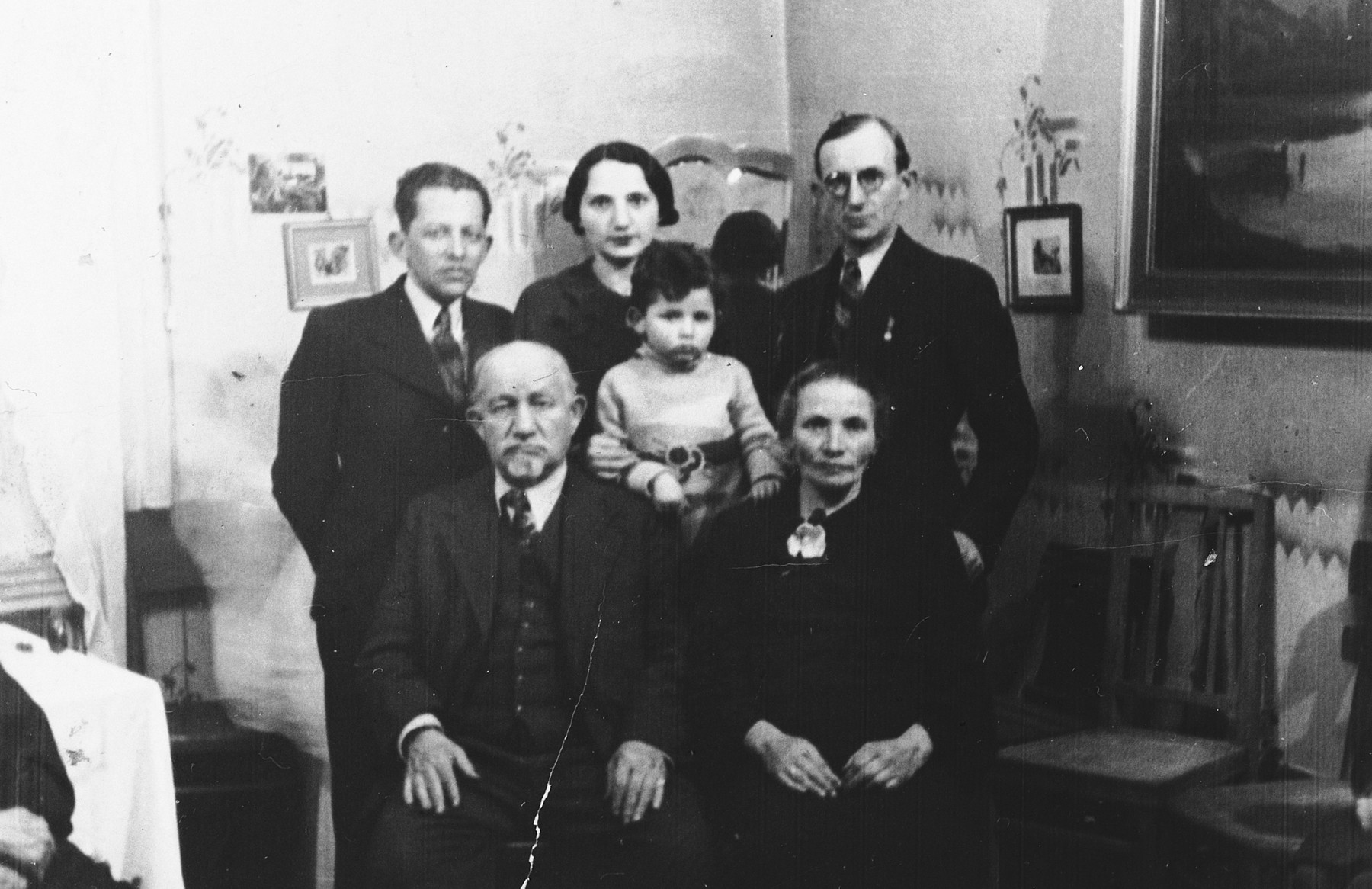 A Polish-Jewish family poses for a group portrait in their home.  Pictured are Leib and Mariam Adler; Schlameck Dunkelblau-Wintergreen; his wife, Erna Adler Dunkelblau-Wintergruen; her son, Jackie Dunkelblau-Wintergruen; and Herman Adler.  None of them survived.