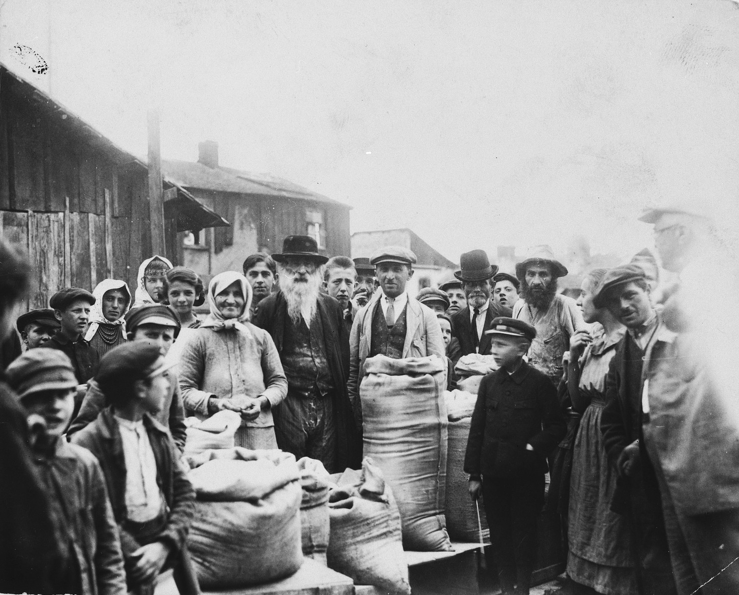 Group portrait of a Jewish family standing in front of the their grains stall in the Drohobycz marketplace.  In the center left are the grandparents of the donor, in the center is the donor's father, Herman Lustig, and on the right is Harry Handel, a relative from America.