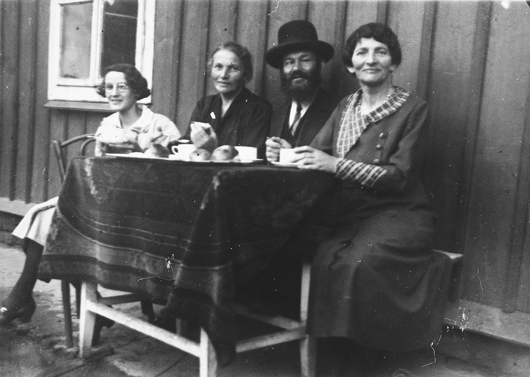 A Jewish family in Pilzno sits outside and enjoys a cup of coffee shortly before the start of the war.  Pictured second from the left is Mariam Silvermann, the donor's maternal grandmother.  Also pictured are her niece, sister and brother-in-law.  Mariam Silvermann was shot and killed in the Rzeszow cemetery together with her daughter Erna Wintergruen-Dunkelblau and her six-year-old son.
