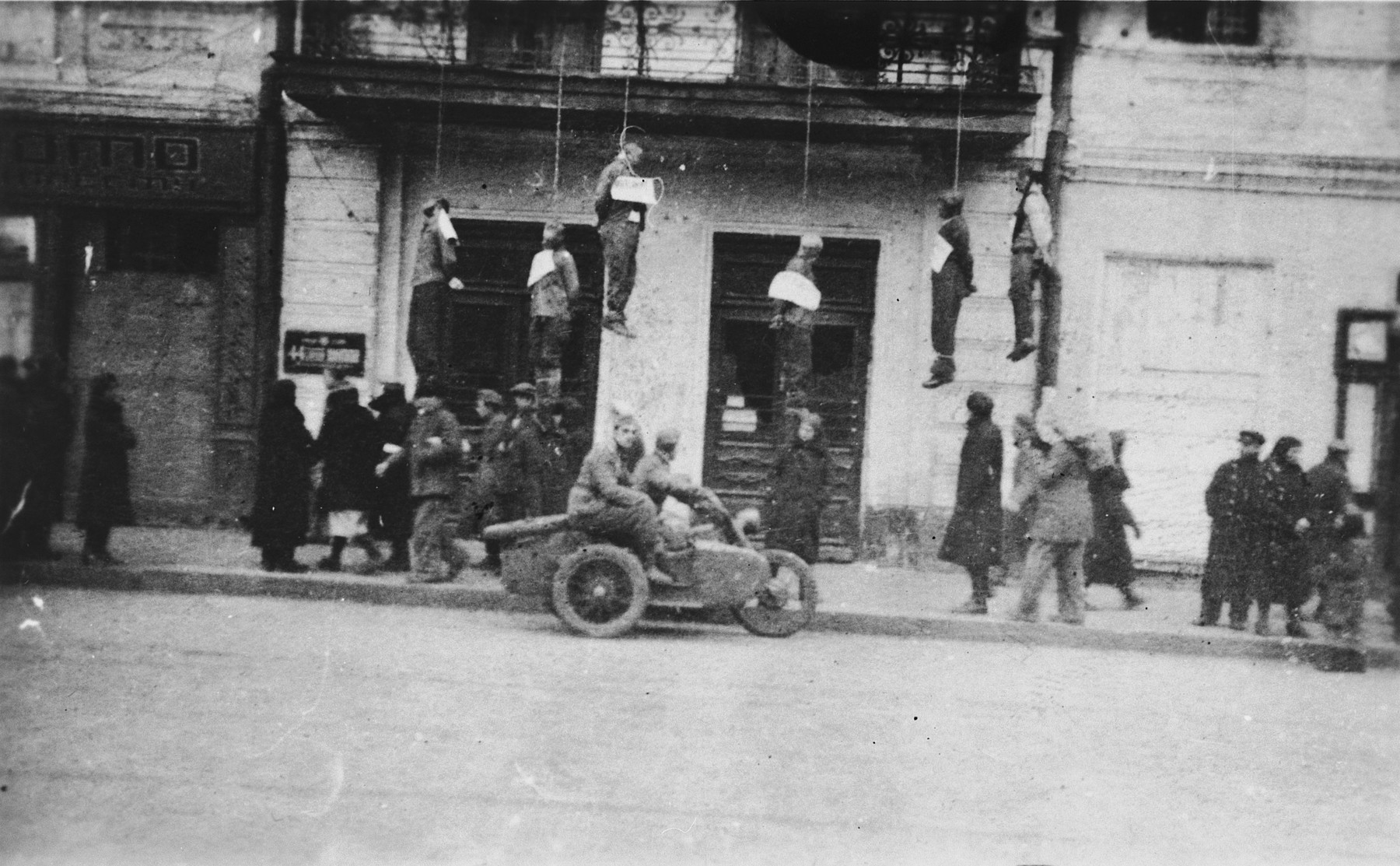 """The bodies of six civilians hang from the balcony of a school on Sverdlov Street where they were executed by German troops of the 50th Army Corps.  The signs around their necks read """"punishment for blowing up an explosives storehouse.""""  The city of Kharkov was captured by the German Sixth Army at the end of October 1941.  Just prior to its fall, the commander of the Sixth Army, General Walther von Reichenau, ordered the commanding officer of the 50th Army Corps to act mercilessly against """"hostile elements,"""" particularly Jews and Bolsheviks.  These segments of the local population were to be subject to collective measures in reprisal for attacks on German personnel or materiel.  Saboteurs in particular were to be publicly hanged as examples.  Thus instructed, the commander of the 50th AK acted vigorously against the local population after a store of explosives blew up in November.  Male Jews, especially, were the target of the wave of arrests and hangings that followed the explosion.  Altogether 200 """"Communists"""" were either shot or hanged and 1000 hostages were taken by the men of the 50th Army Corps."""