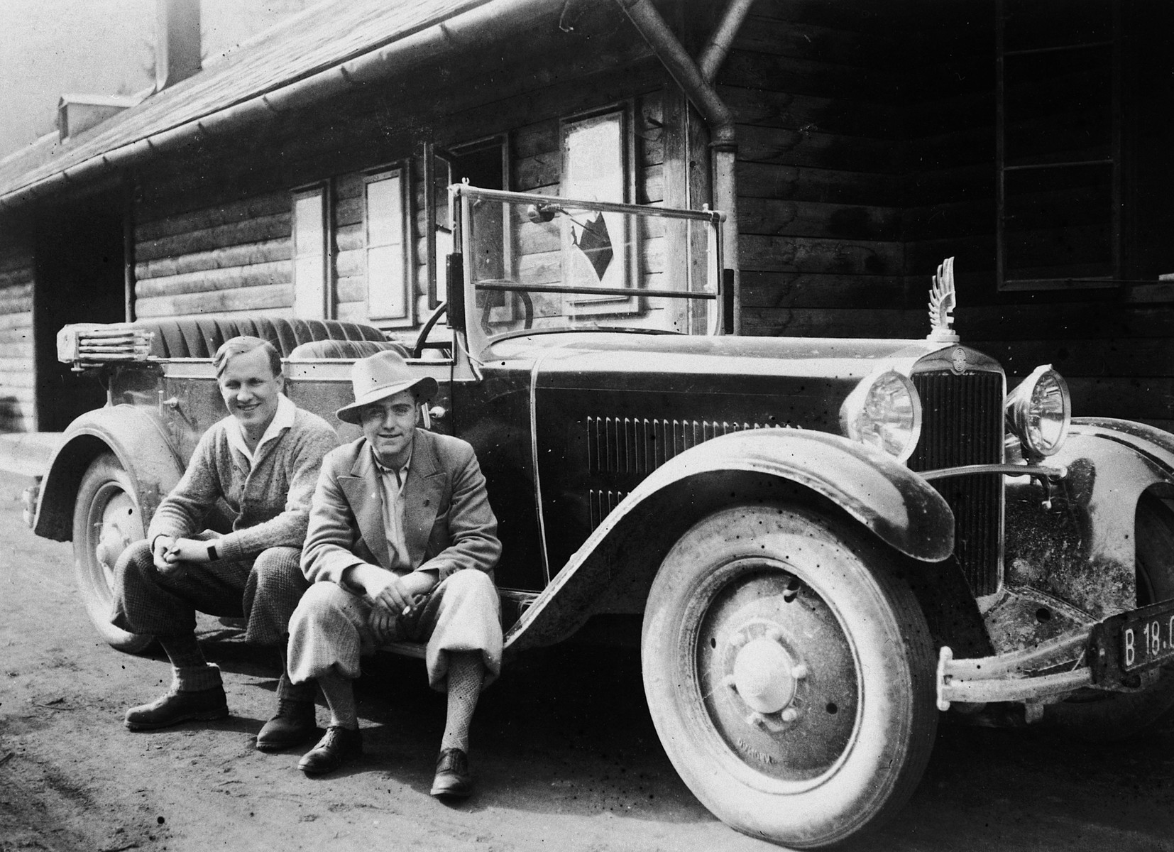 Two Austrian men pose next to a brand new, large automobile which they purchased for use as a taxicab.  Pictured in front is Ernst Porges, uncle of the donor.