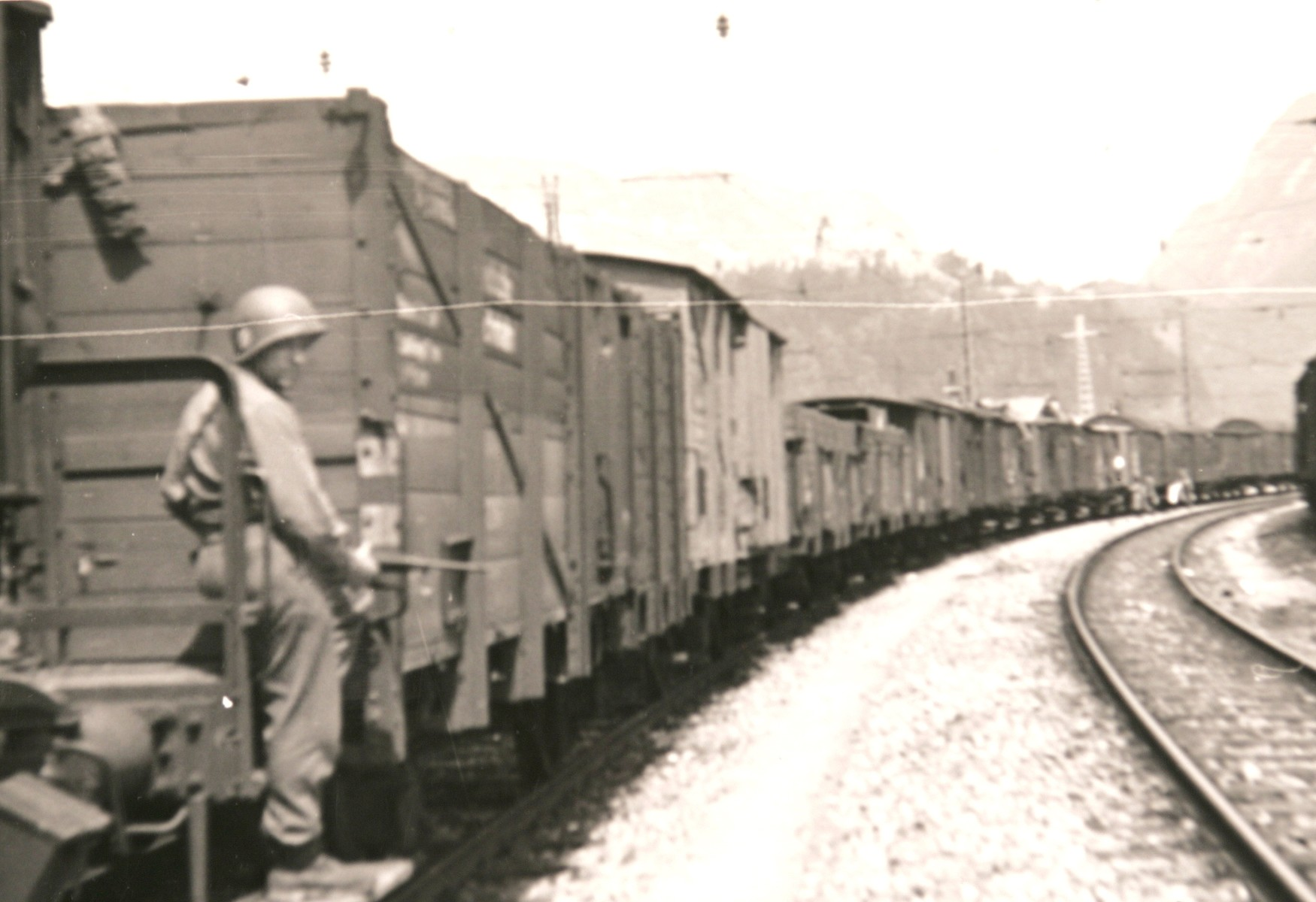 "An American soldier guards the Hungarian Gold Train in Werfen, Austria, soon after the American occupation authorities took custody of the train.  The original caption reads: ""The Hungarian train of loot; view of freight cars."""